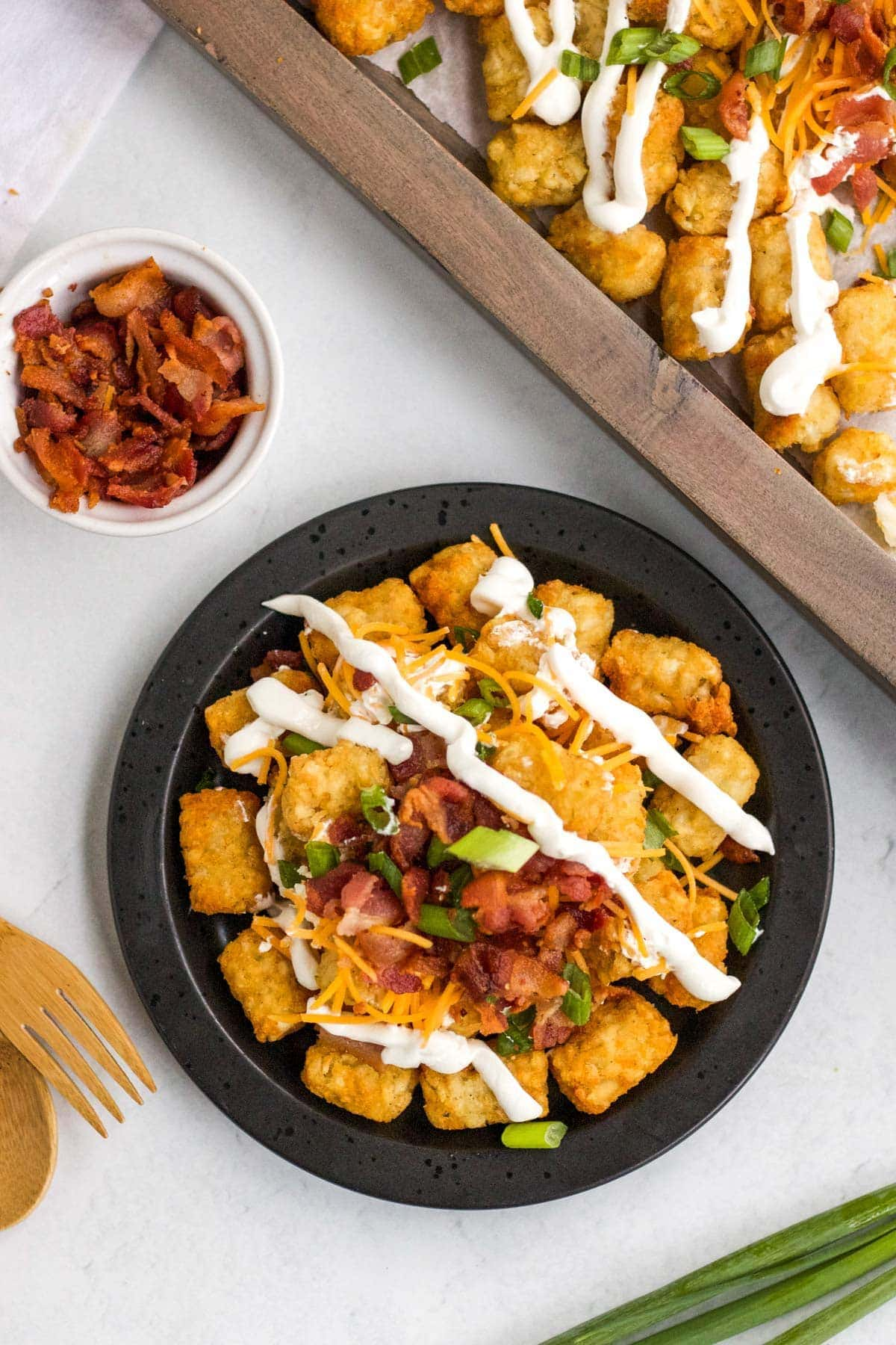 tater tot nachos with sour cream, bacon, green onions and cheese, black plate, wood tray