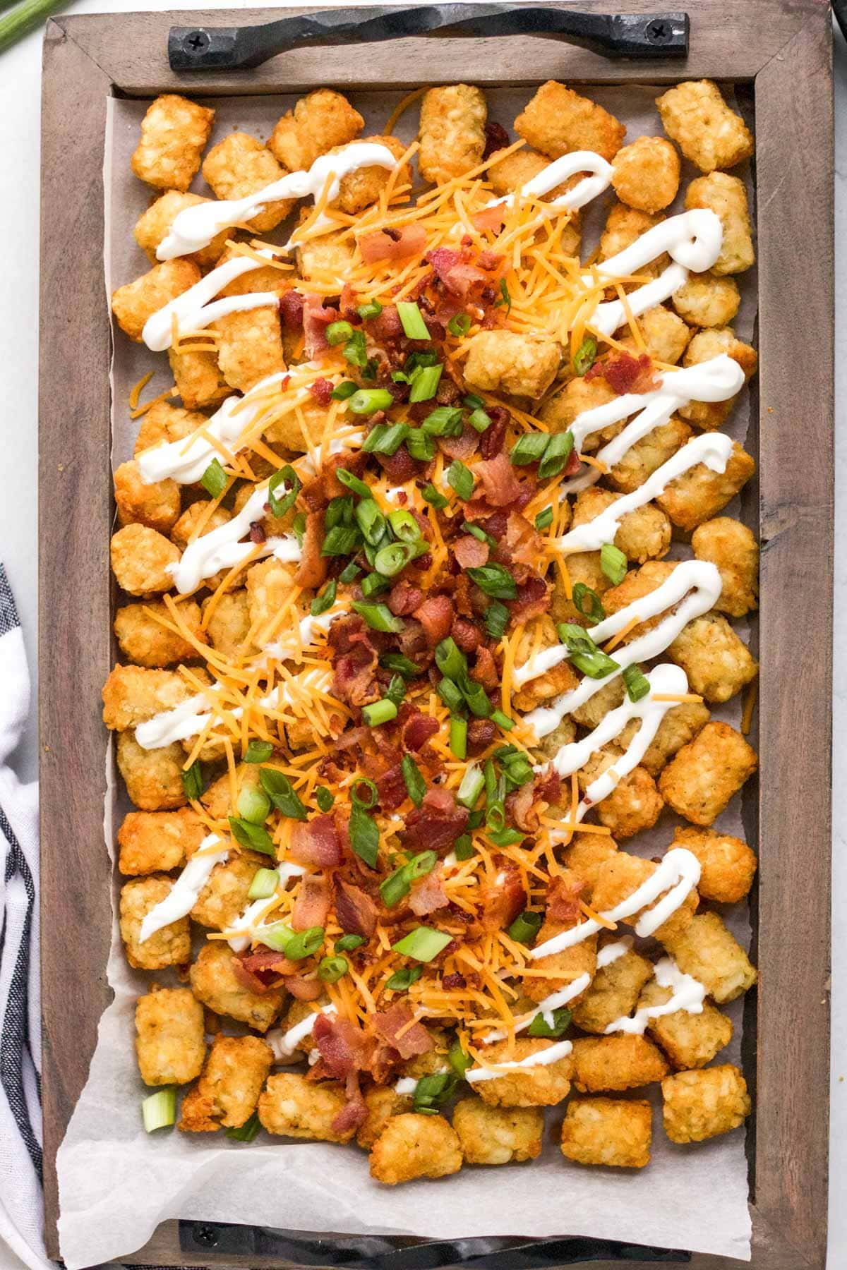 tray of tater tots with cheese, sour cream, green onions and bacon
