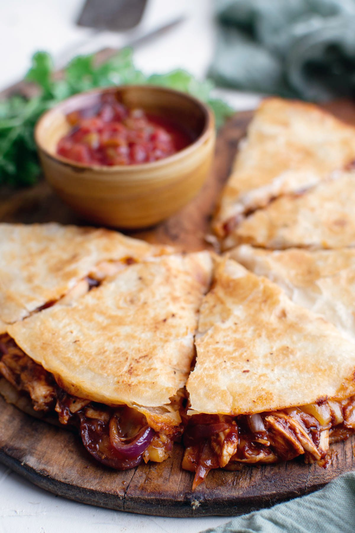 sliced bbq chicken quesadilla with dish of salsa on wood cutting board