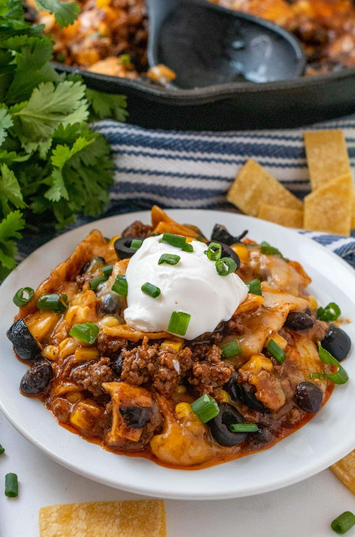 white bowl, skillet enchiladas, sour cream, olives, green onions, cheese, ground beef, cast iron skillet ,tortilla strips