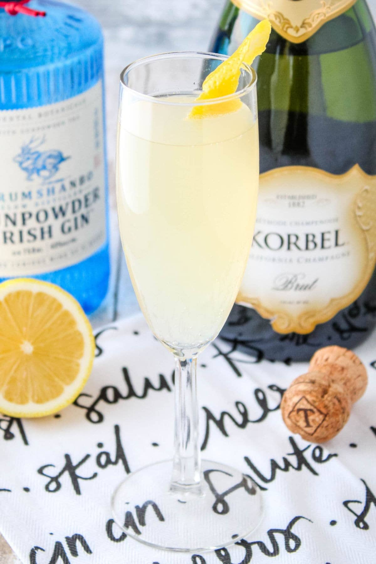 close up of a french 75 in front of gin and champagne bottles