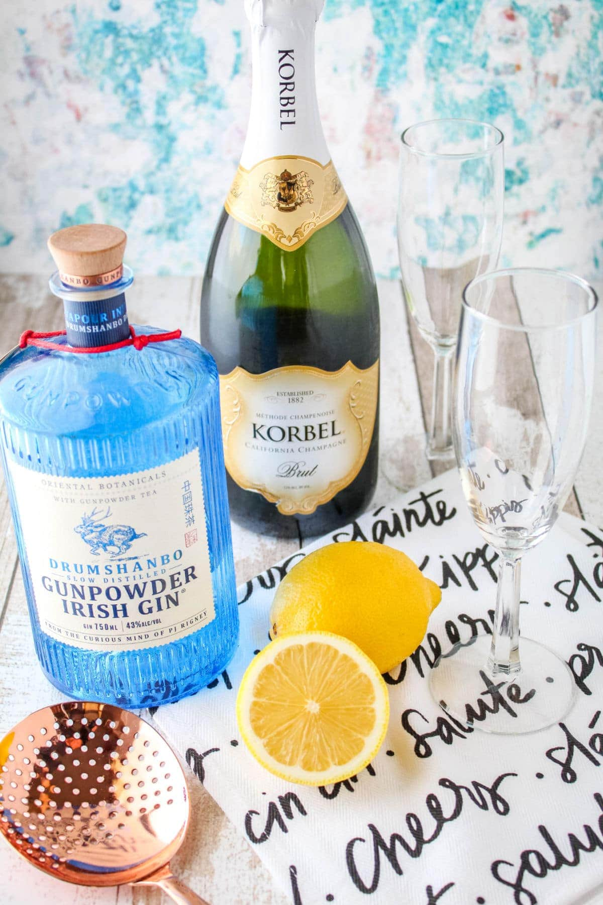 ingredients to make a French 75 cocktail next to champagne flutes