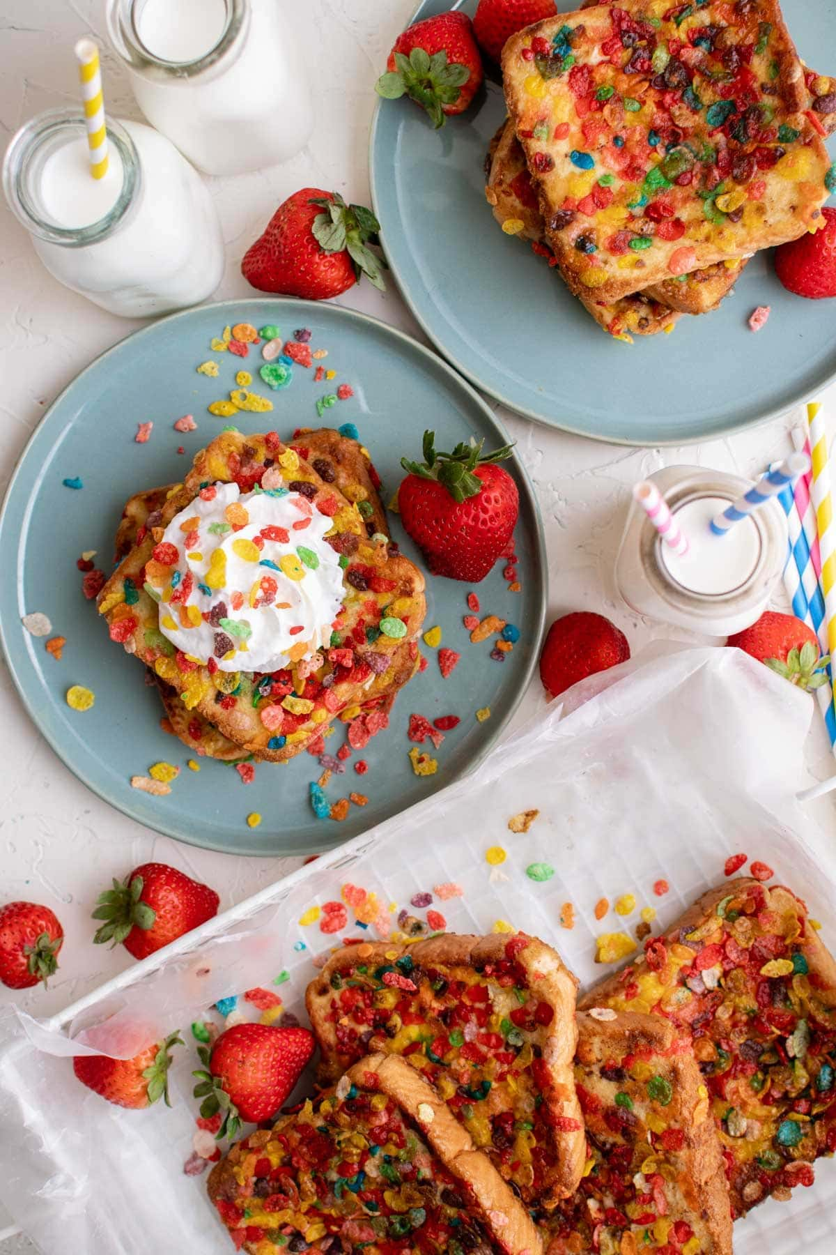 blue plates, glasses of milk, fruity pebbles, whipped cream, strawberries