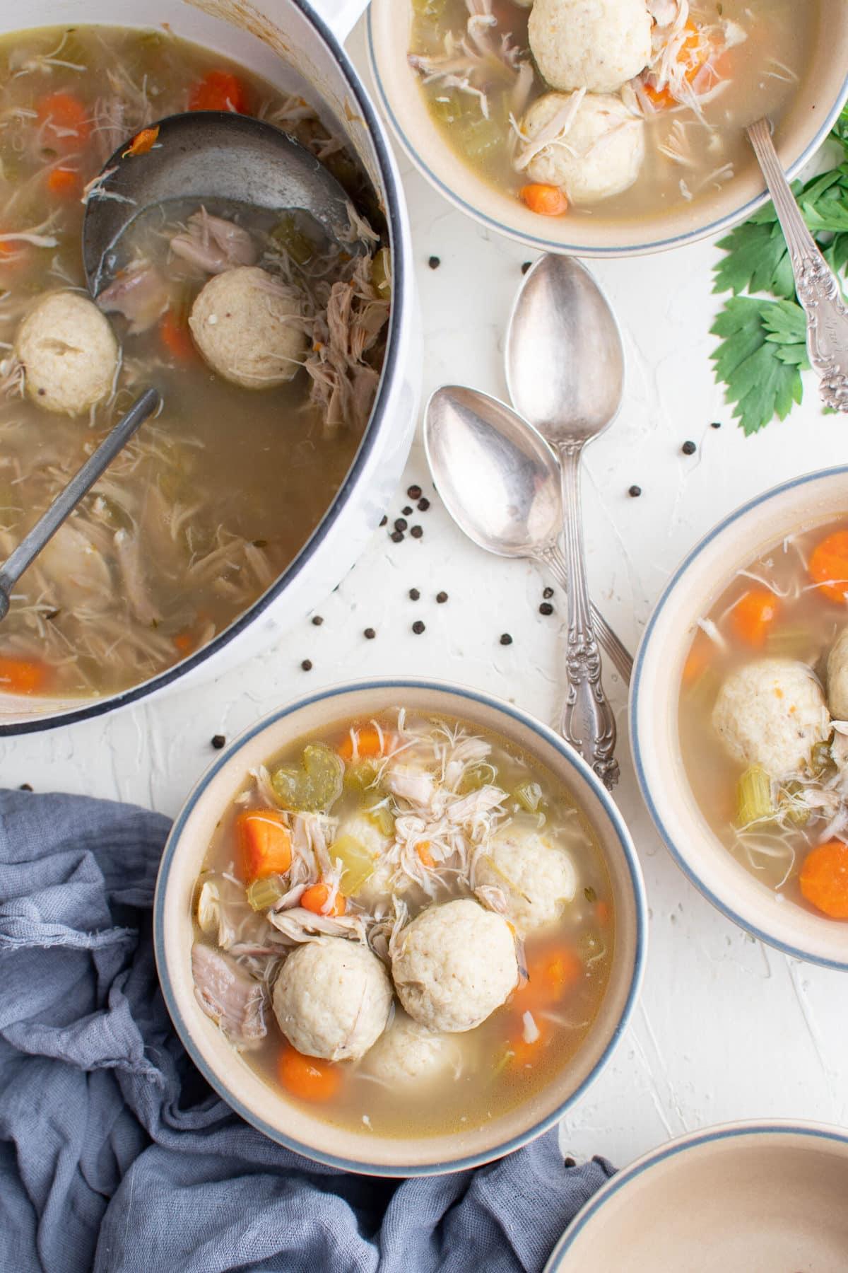 white bowl, matzo balls, pot of soup, spoons, parsley, blue napkin