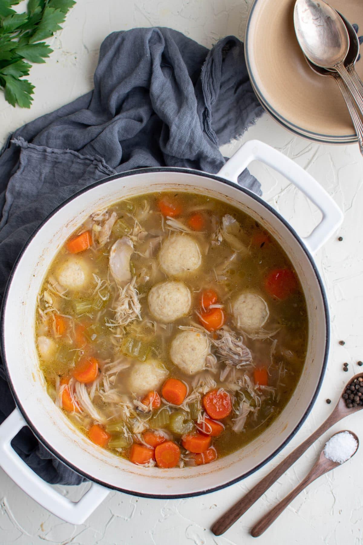 white soup pot, chicken sou and matzo balls, blue napkin, parsley