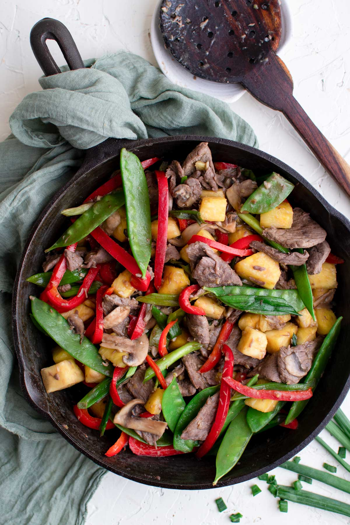 black skillet, green napkin, wood spoon, vegetables and beef in a skillet