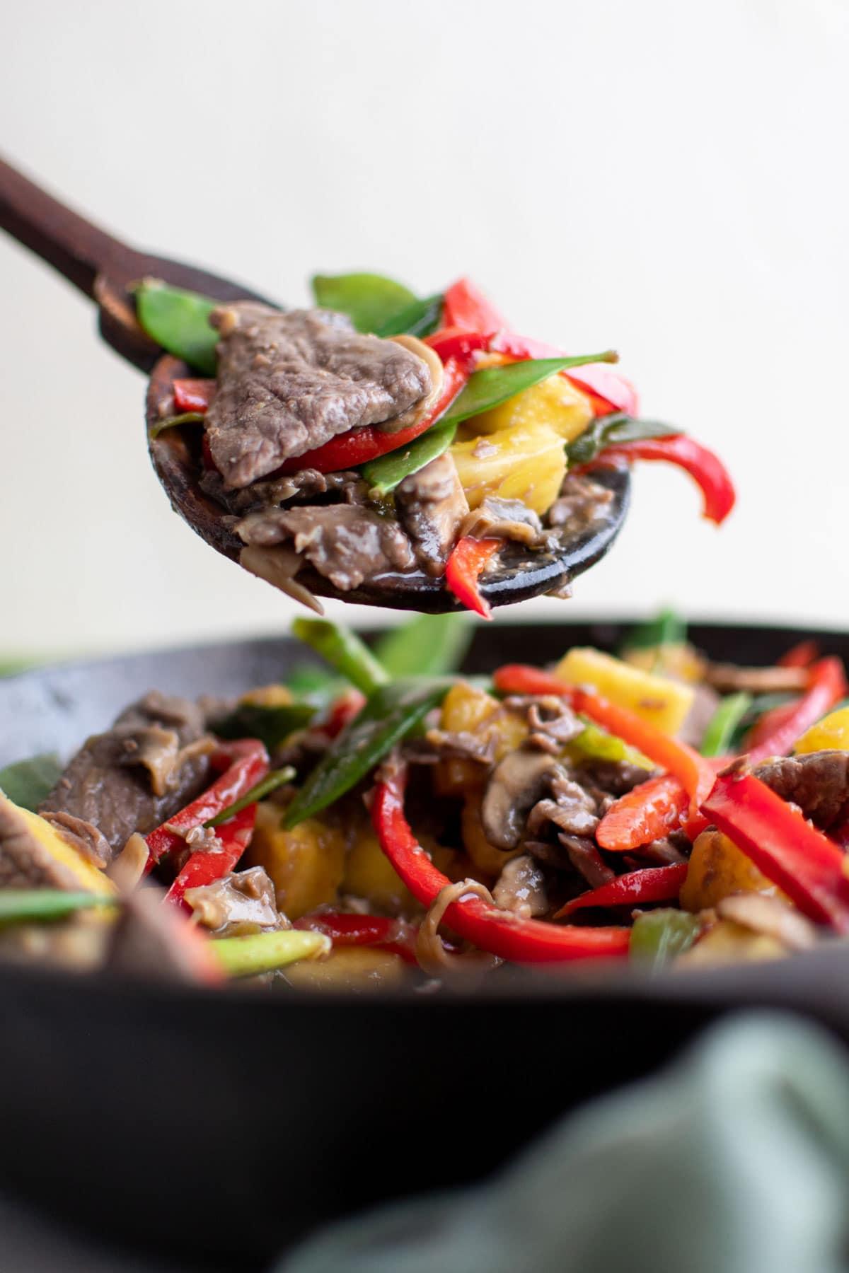 skillet with pineapple beef stir fry, wood spoon