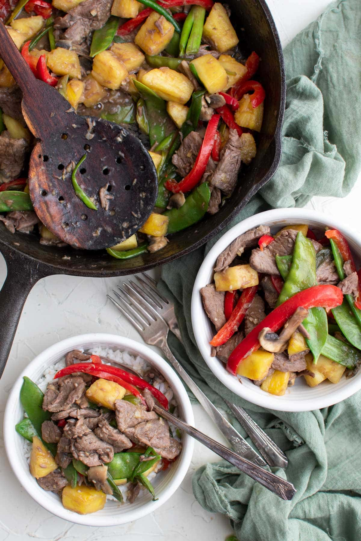 white bowls with beef, stir fry vegetables, green napkin, black skillet, wood spoon
