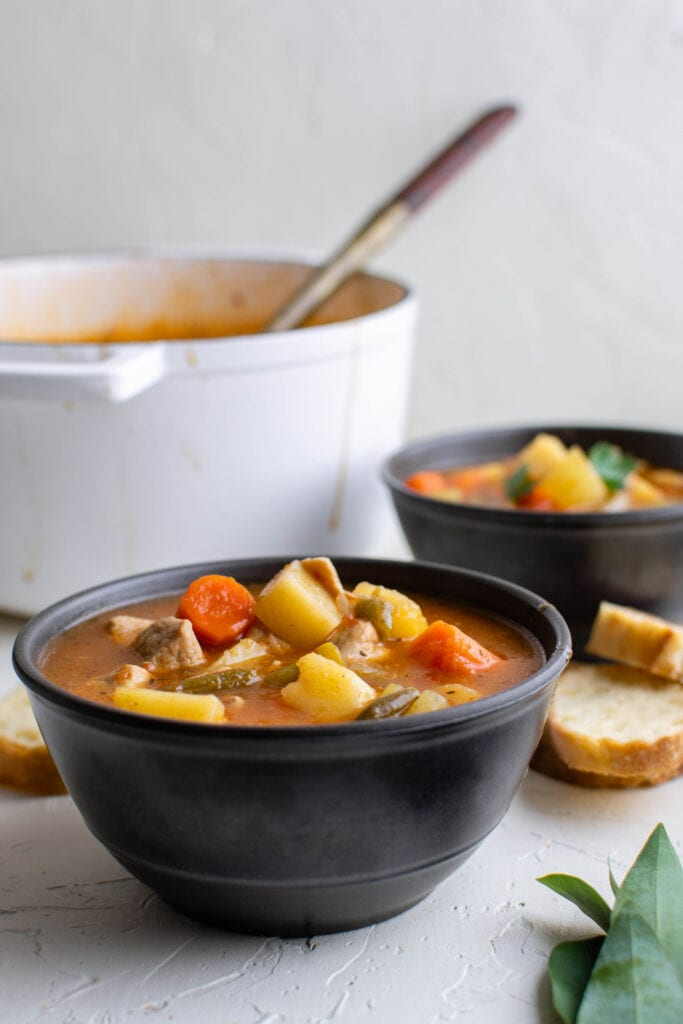 pork stew in bowls and a pot