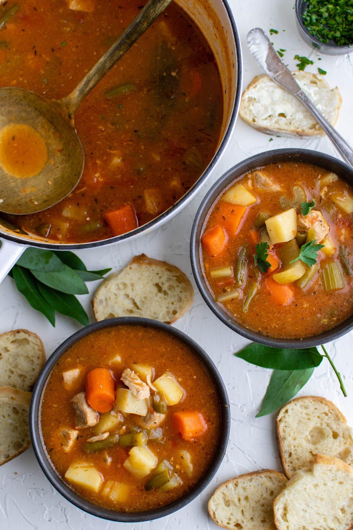 pork stewm blue bowls, white soup pot, slices of bread .spoons