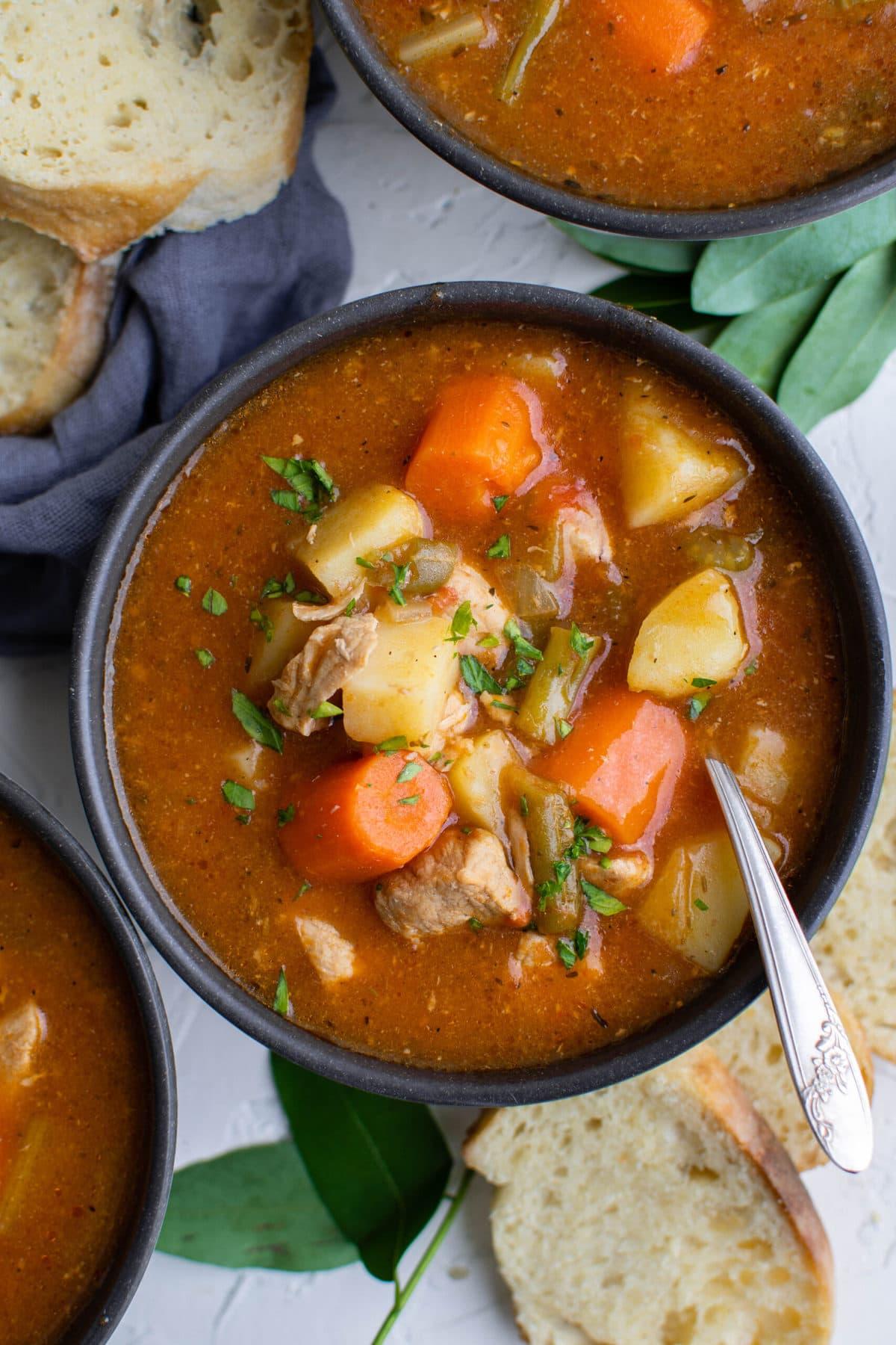 black bowls, potatoes, pork, carrots, blue napkin, bay leaves, bread