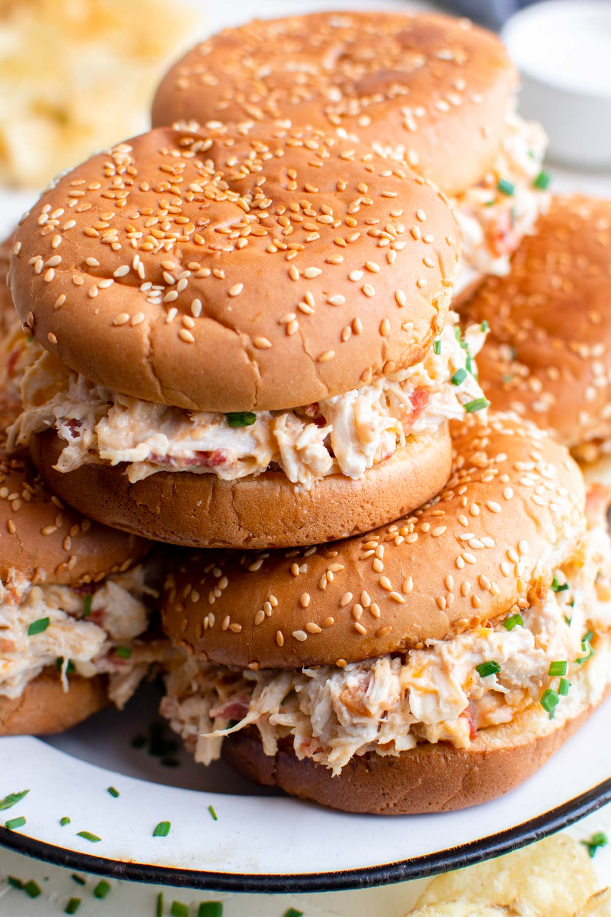shredded chicken sandwiches with sesame seed buns, white plate, potato chips