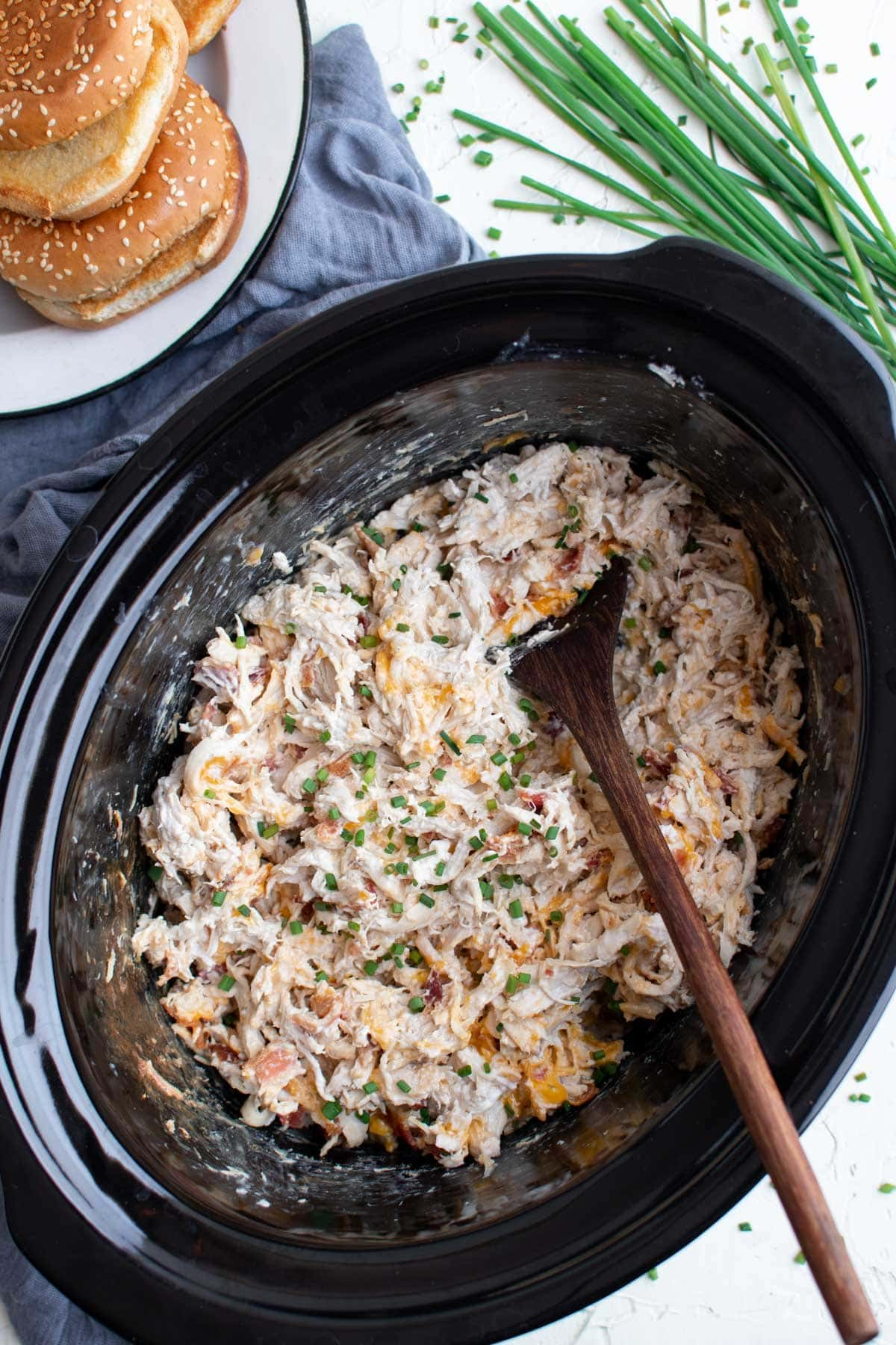 slow cooker pot with creamy shredded chicken, wooden spoon, stack of sesame seed buns, chives