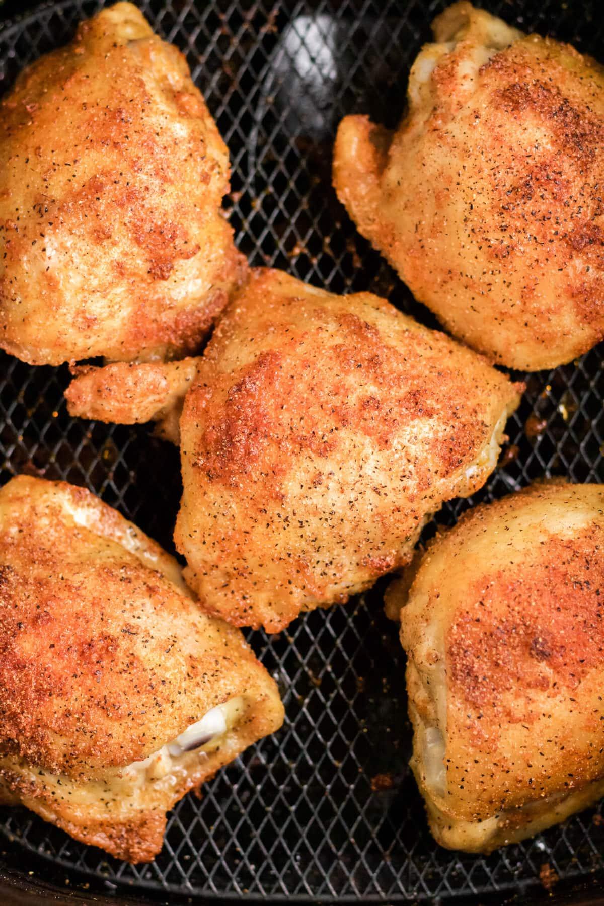 chicken thighs with crispy skin in air fryer basket