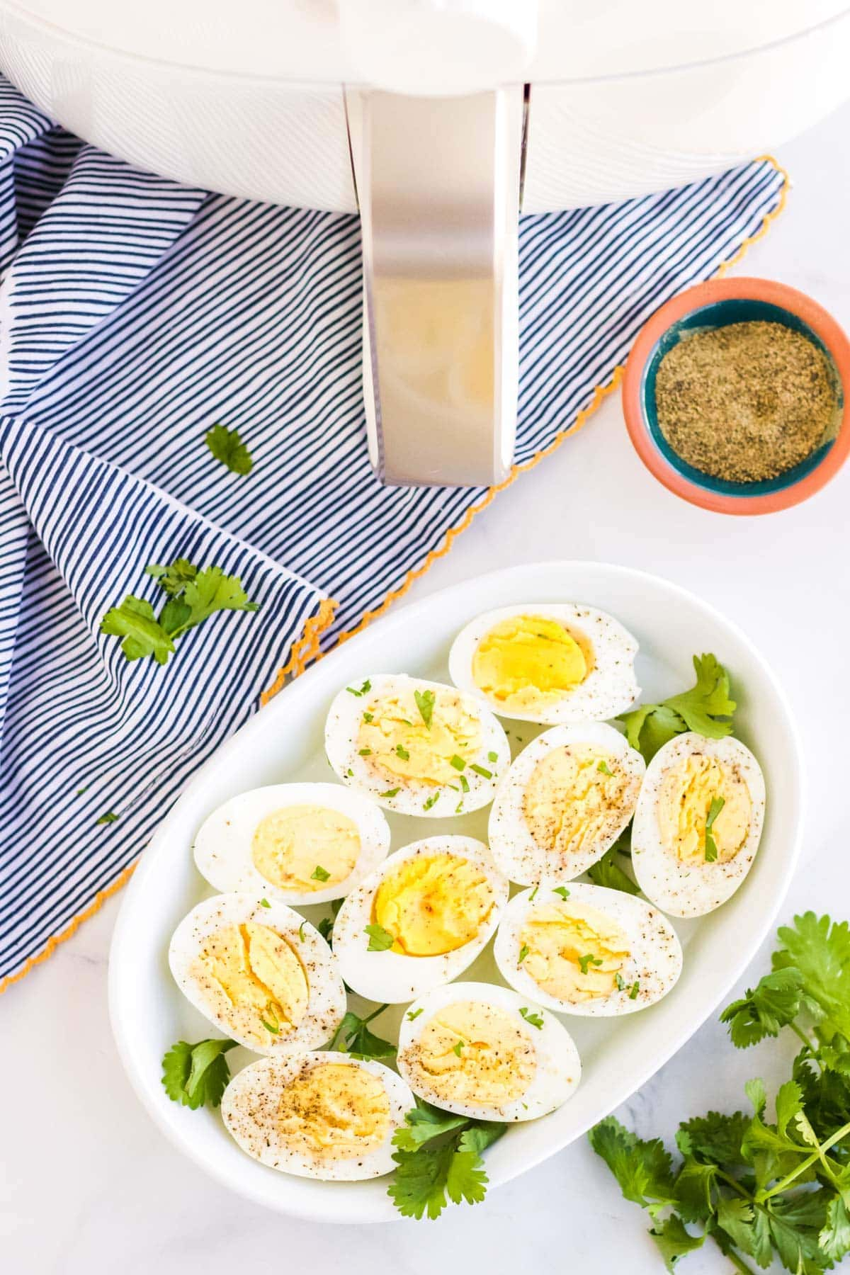 air fryer, white platter of sliced hard boiled eggs, pepper, parsley, blue towel