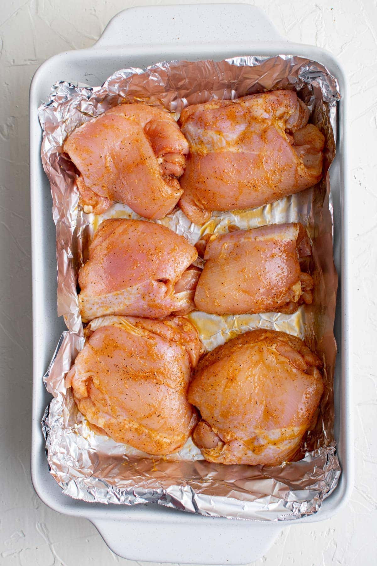 raw boneless chicken thighs, baking dish with foil