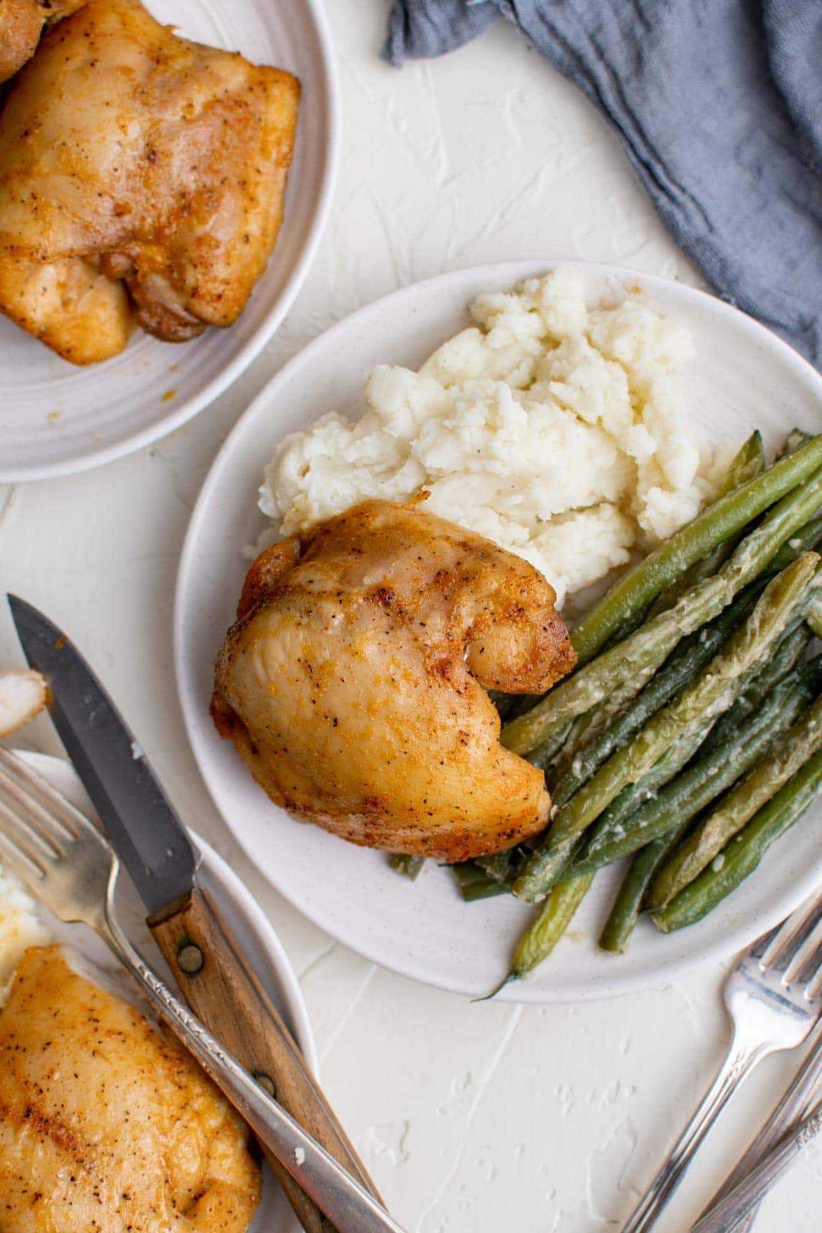 white plates, chicken thighs, green beans, mashed potatoes, forks