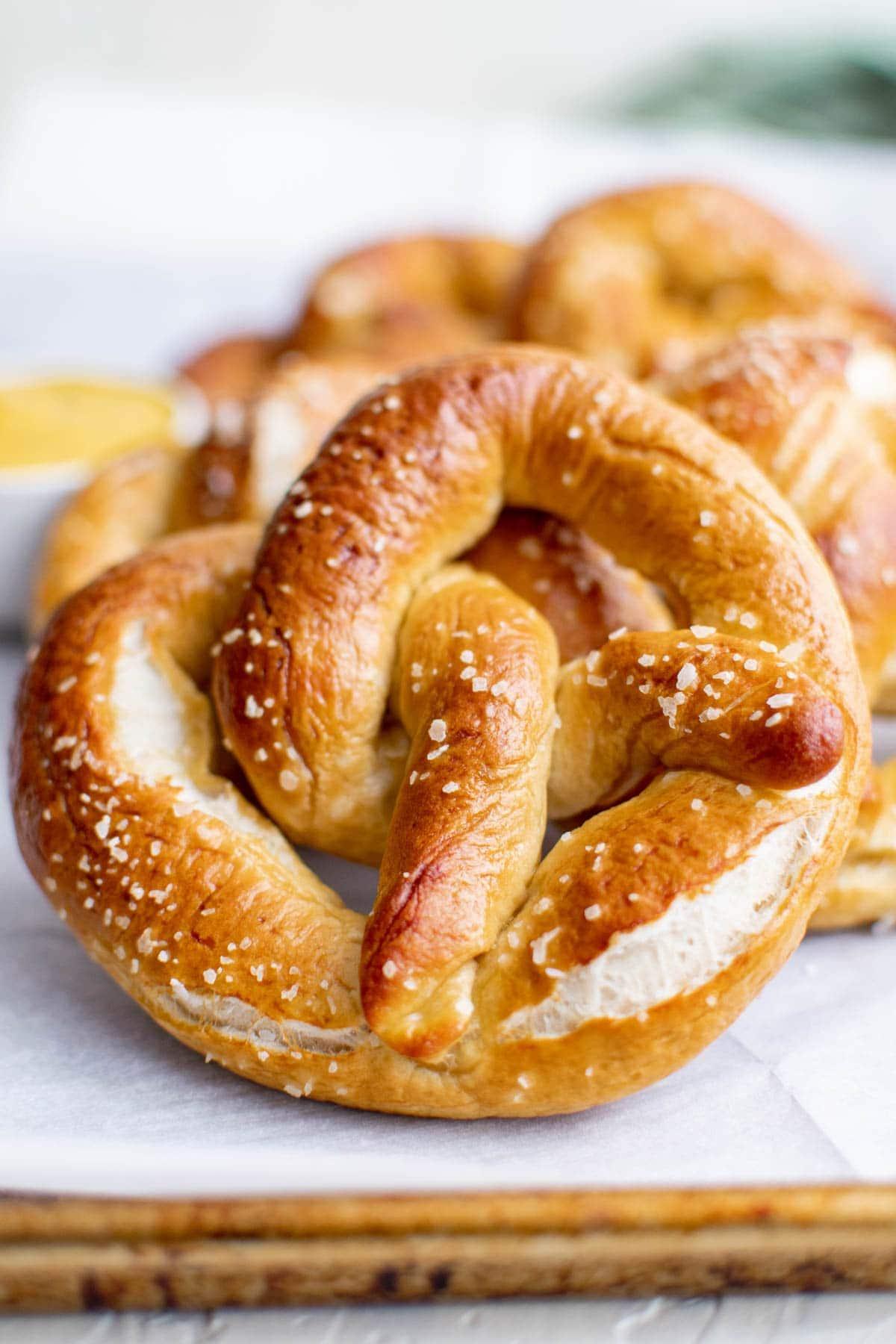 soft pretzels baked with salt, wood cutting board, parchment paper