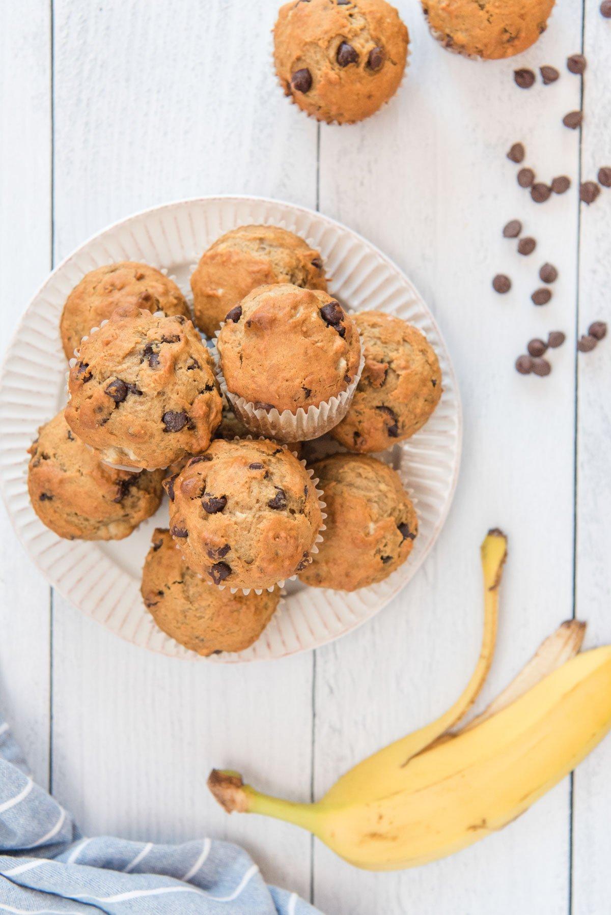 chocolate chips, banana, white plate, chocolate chip banana muffins, white wood background