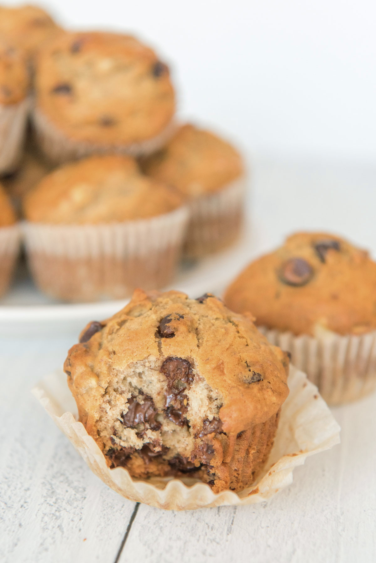 chocolate chip muffin, muffin wrapper, white plate and stack of muffins,