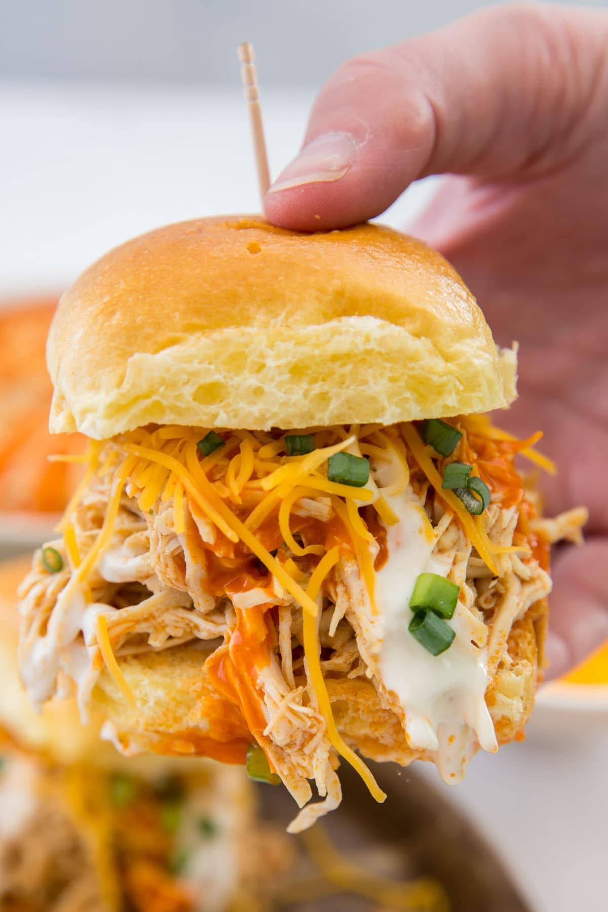 hand holding a buffalo chicken slider with a toothpick
