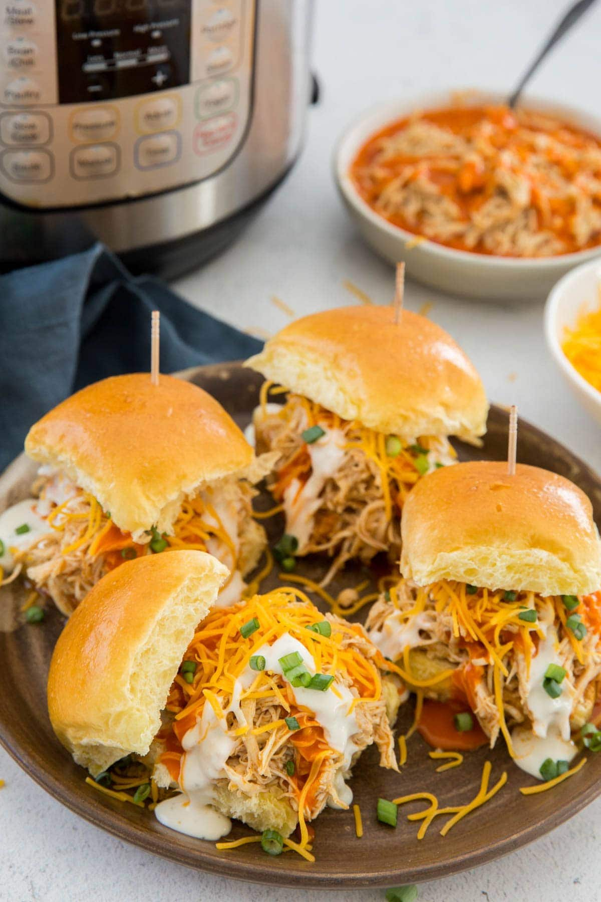 buffalo chicken sliders, shredded cheese, ranch dressing, green onions, instant pot, white bowls