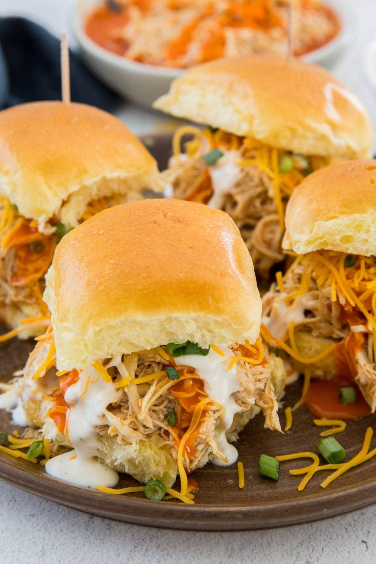 buffalo chicken on slider rolls with green onions, ranch and cheese, toothpicks
