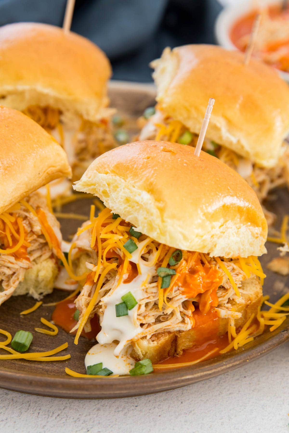 buffalo chicken on slider rolls with green onions, ranch and cheese, toothpicks, gray plate