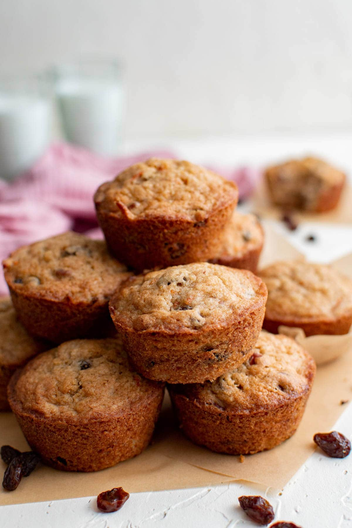 carrot cake muffins stacked on top of one another, parchment paper, raisins