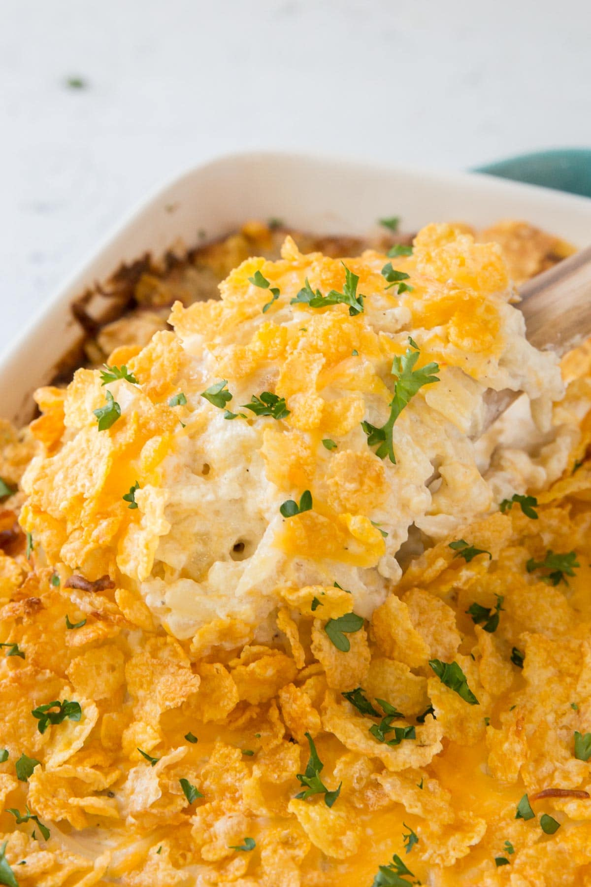 hashbrown casserole with corn flakes topping, wooden spoon, parsley