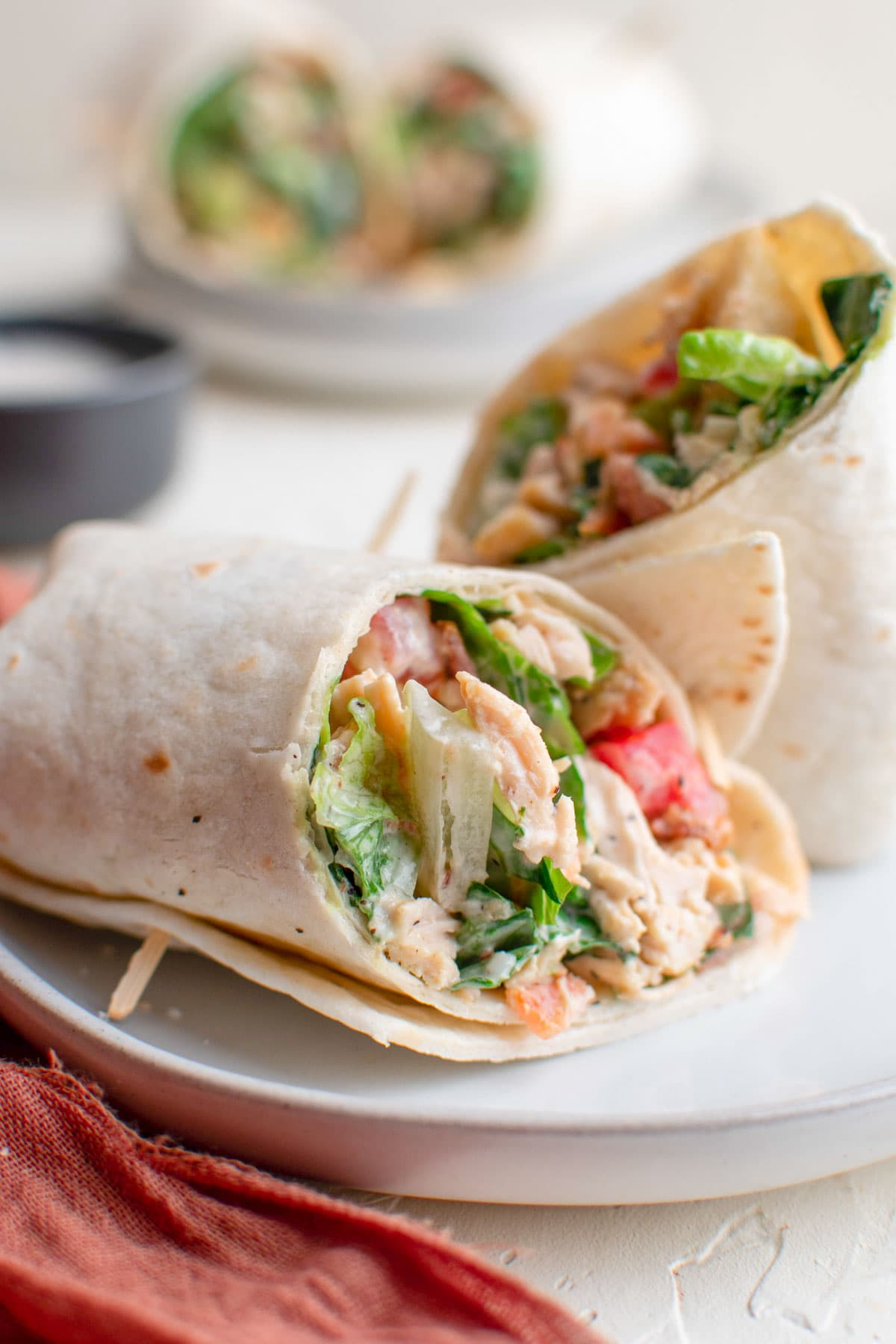 white plates, pink napkin, chicken wraps with lettuce and tomatoes, toothpicks