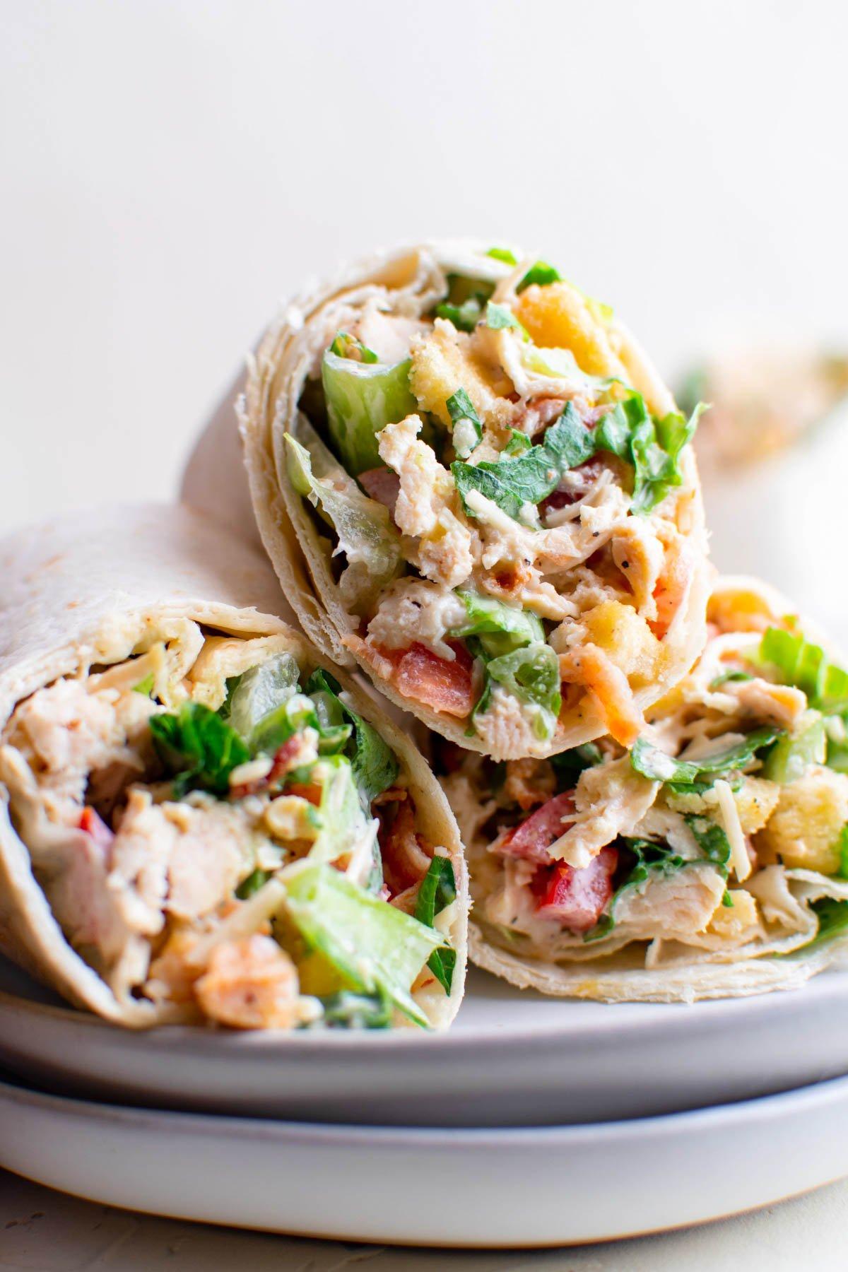 chicken caesar salad in tortillas with toothpicks, white plates