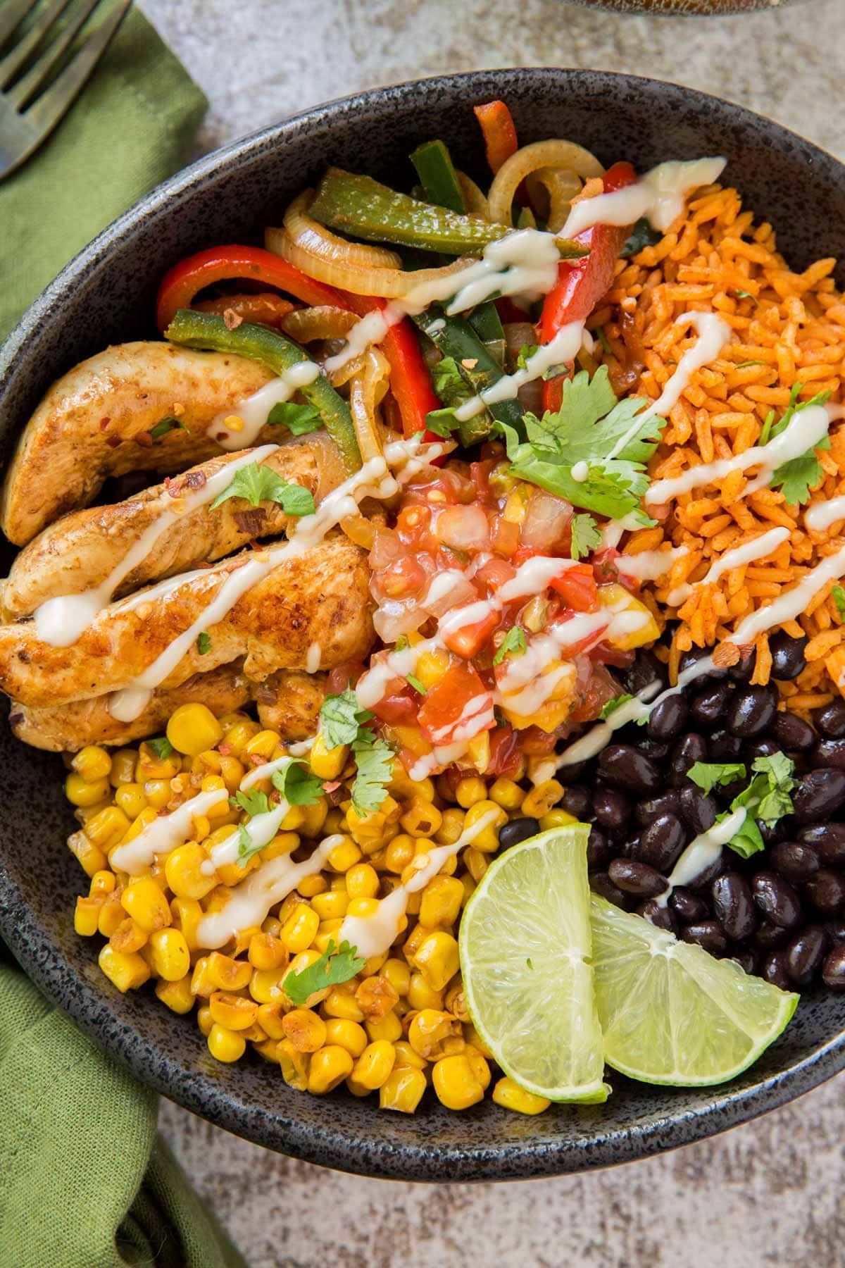bowl with chicken fajitas bowl with limes, corn, black beans rice and peppers
