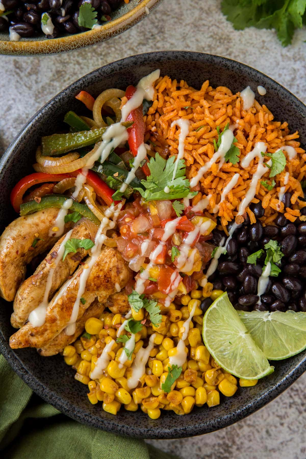 black bowl with chicken fajitas, corn, black beans, peppers and limes
