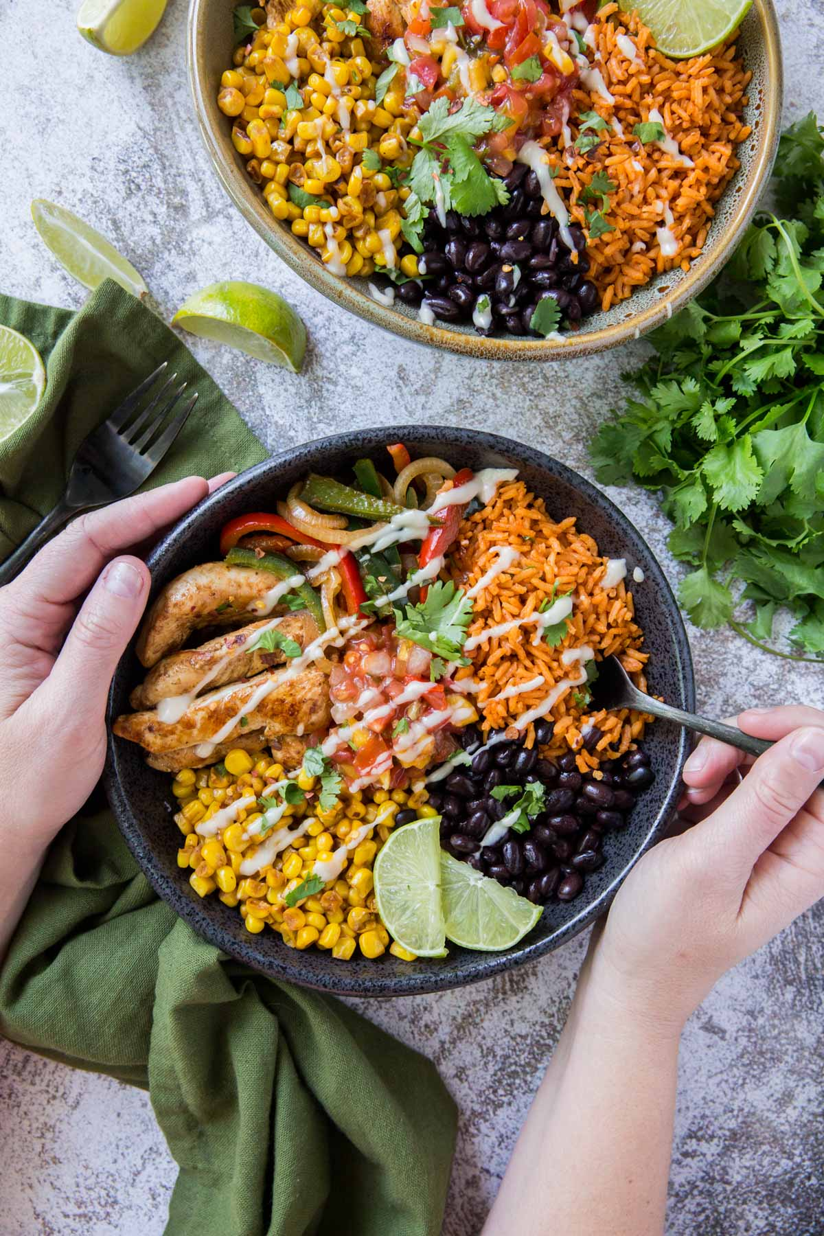 hands holding a black bowl with fajita chicken, rice, limes, beans, and peppers