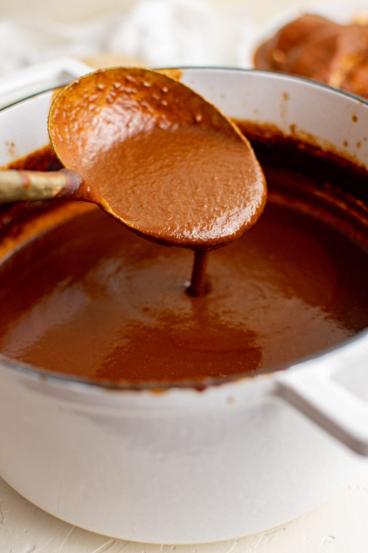 white pot with mole sauce and a large spoon