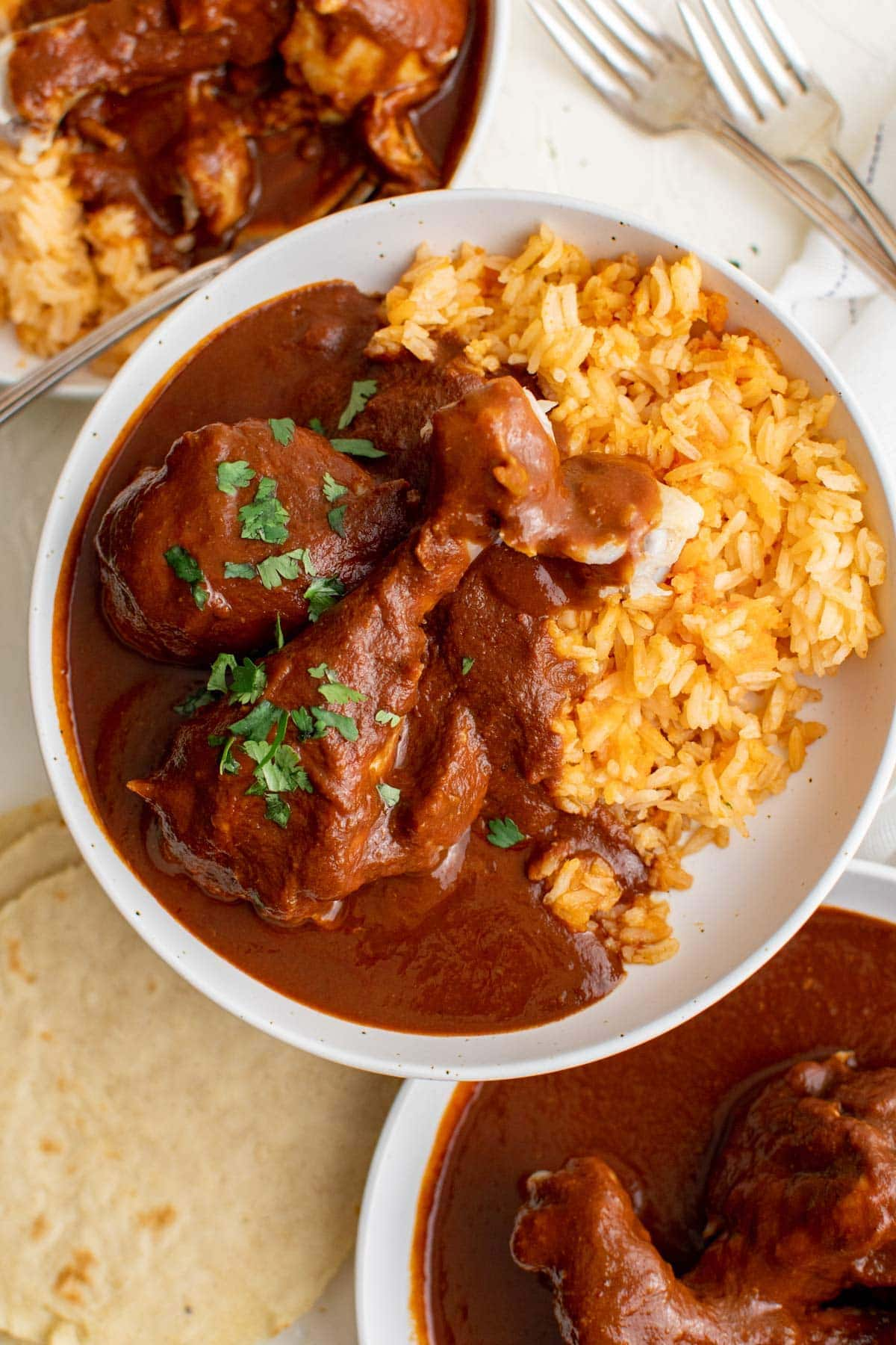 white plate, chicken with mole sauce, mexican rice, forks