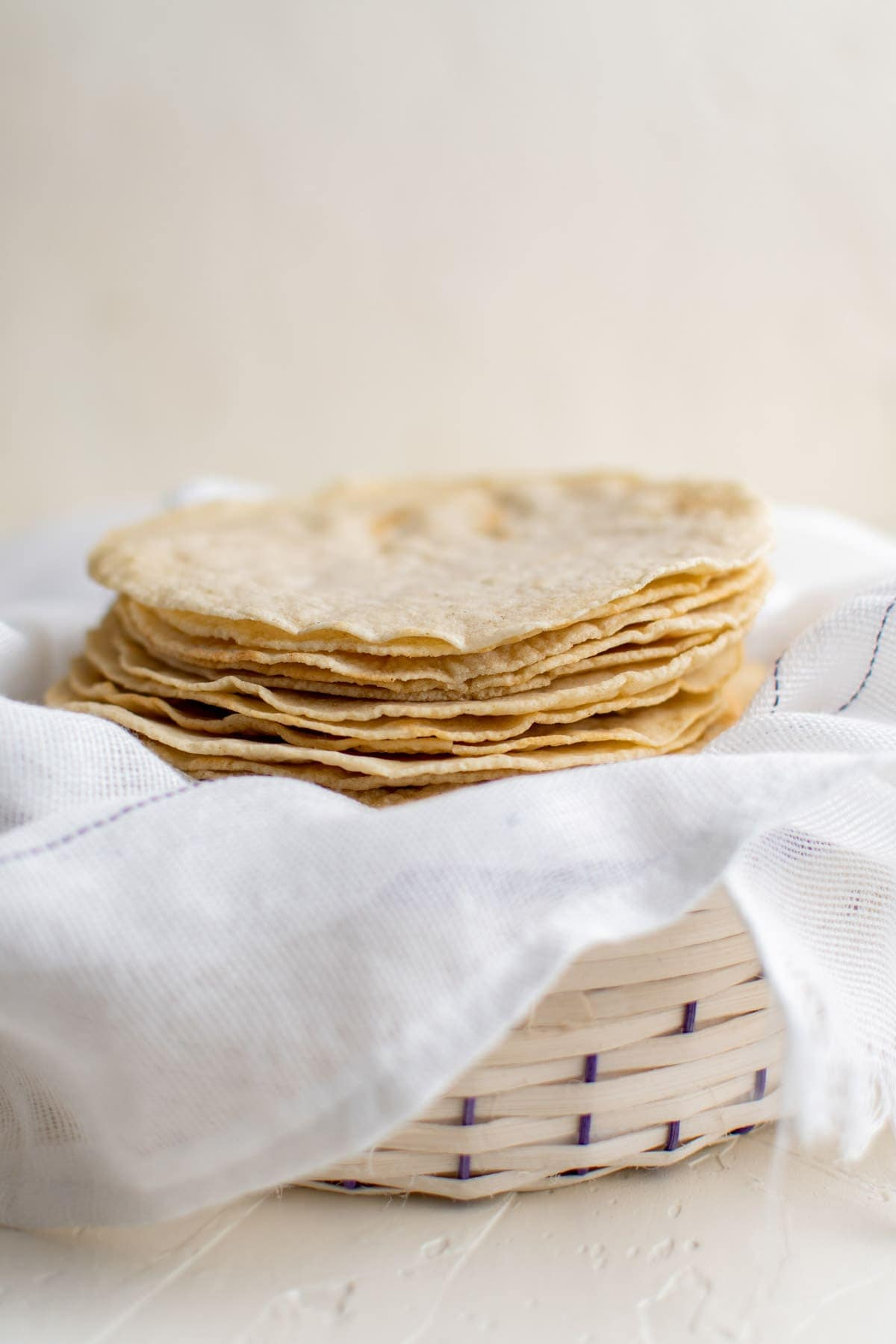 corn tortillas stacked in a white basket with a white towel