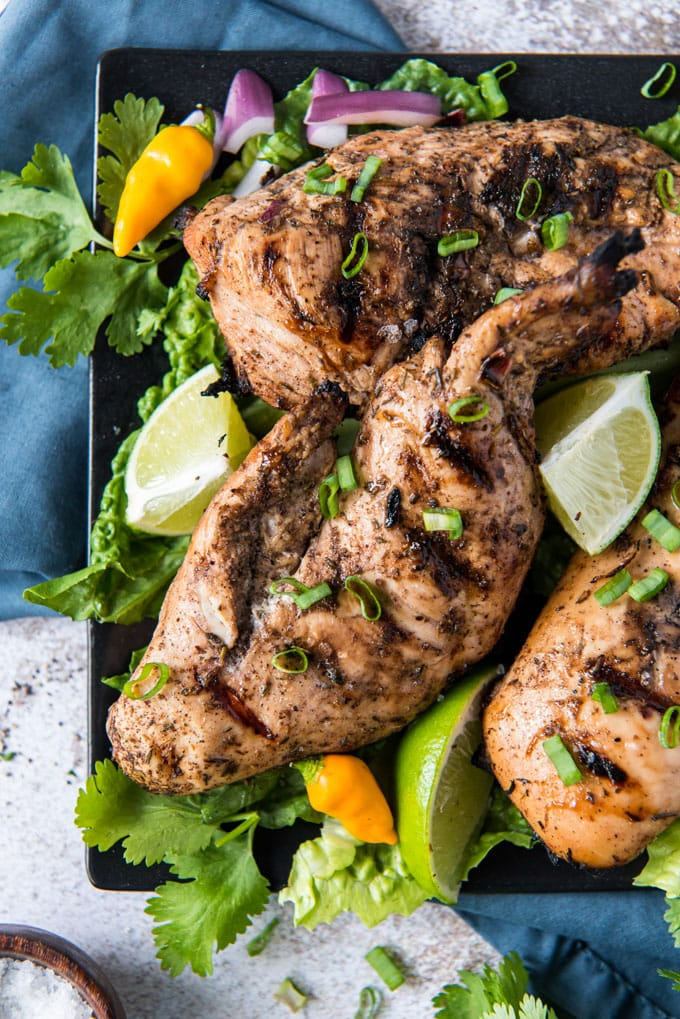 grilled jerk chicken on a black platter with limes and onions