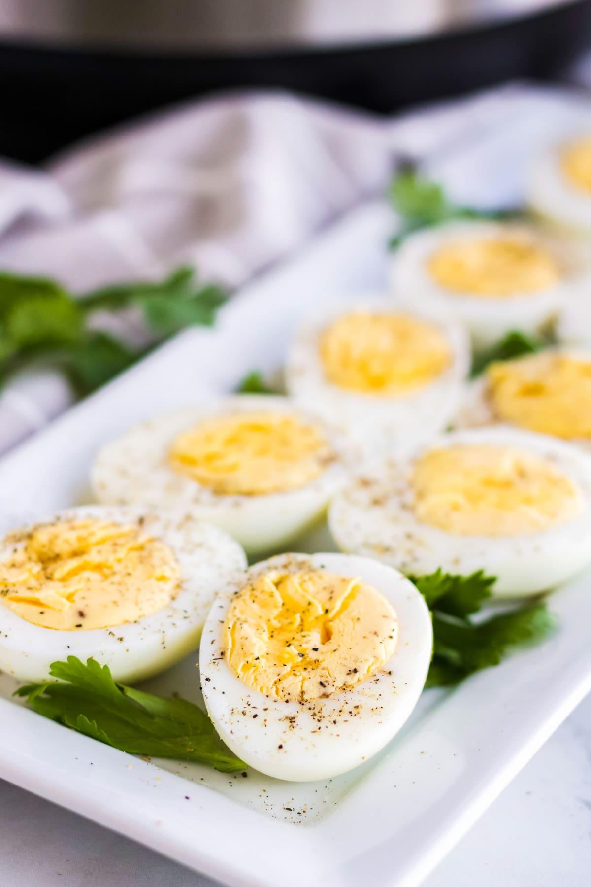 hard boiled eggs, sliced in half, instant pot, white platter, white towel, pepper