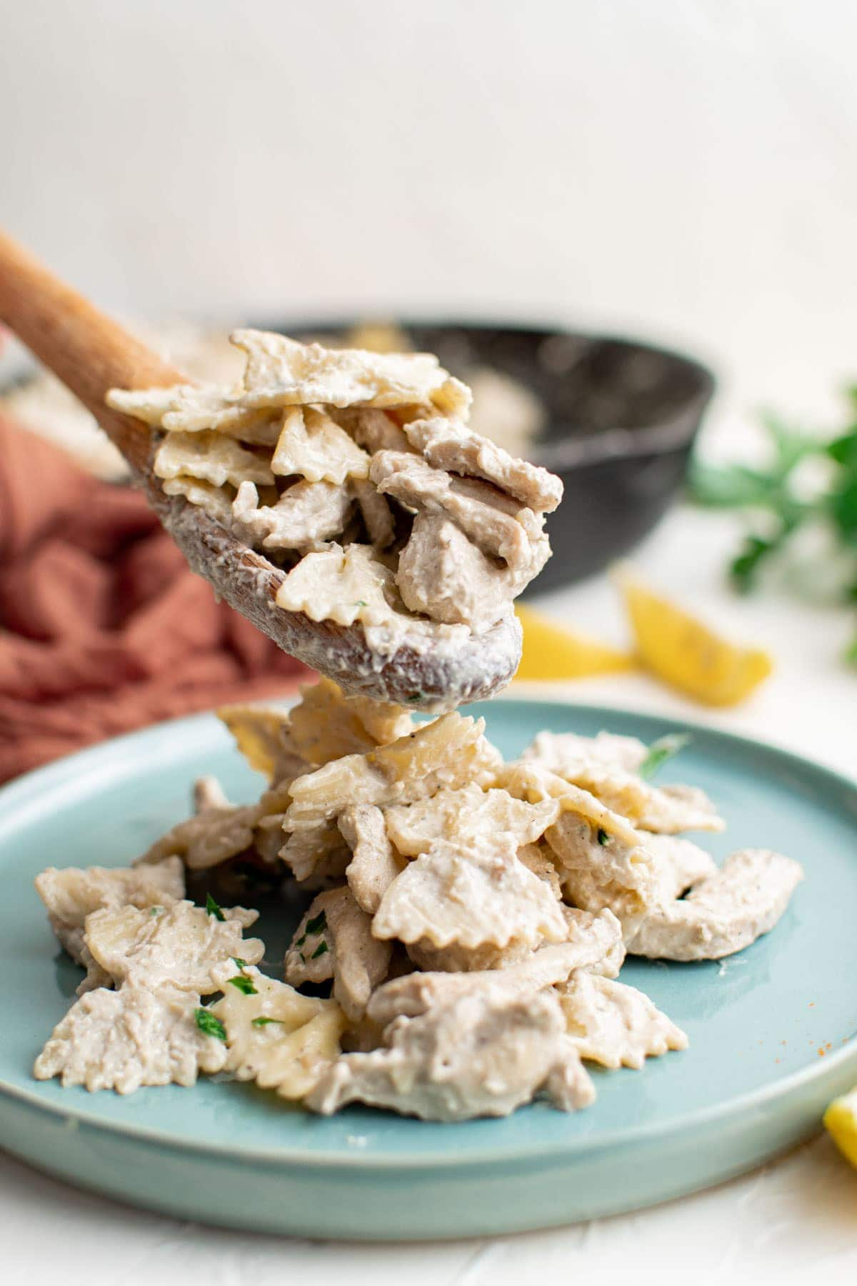 creamy chicken pasta, lemons, wooden spoon