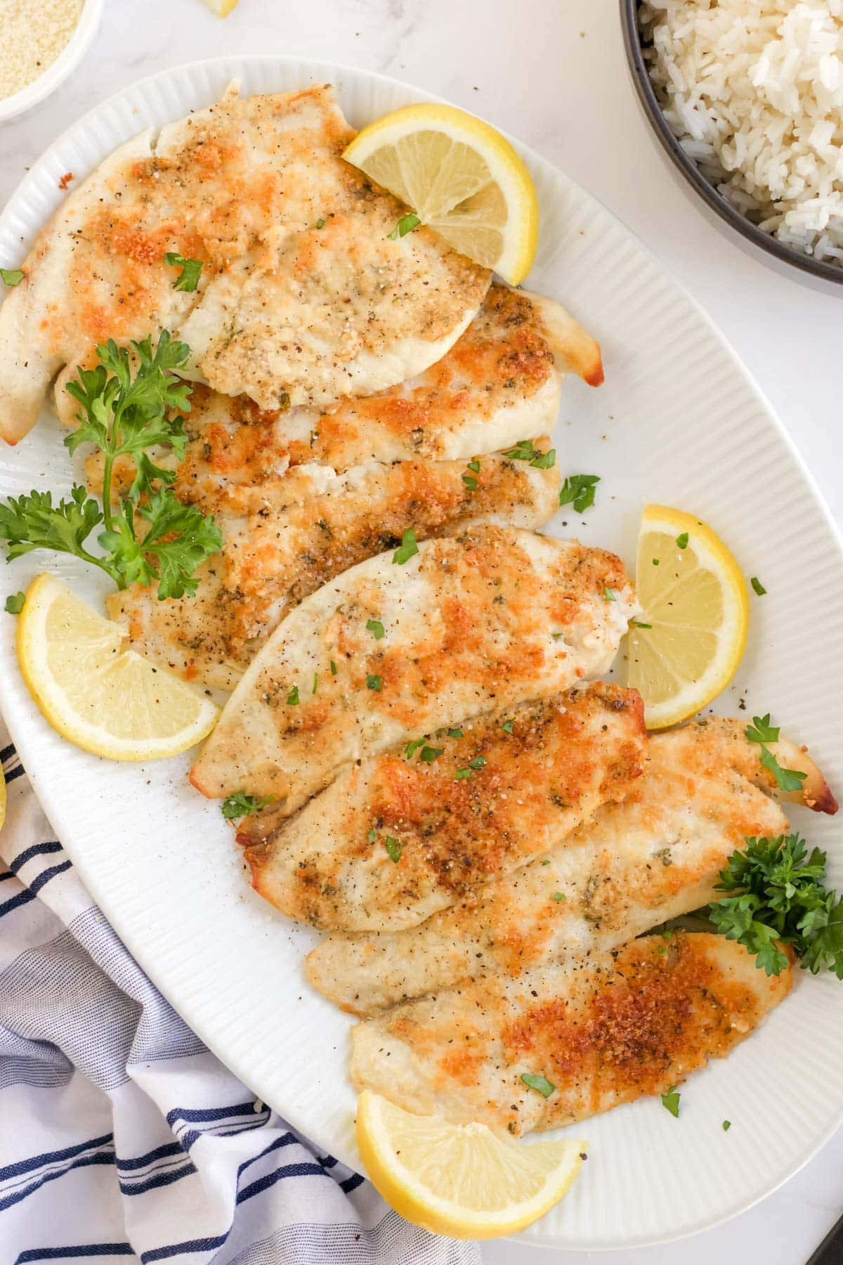 white platter of parmesan crusted tilapia, lemon slices, parsley