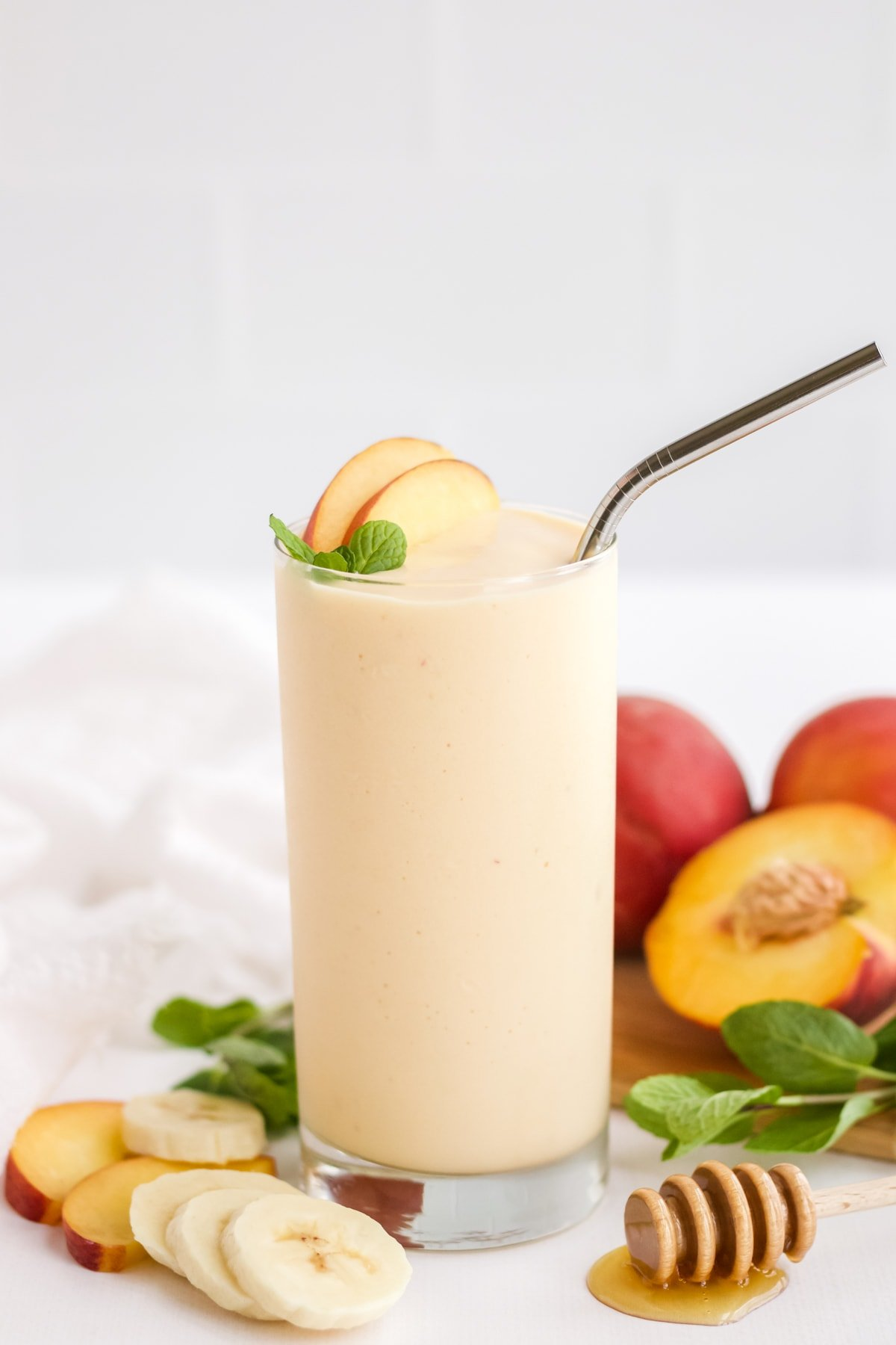 Peach Smoothie on a white styling board with ingredients laid out around the glass.