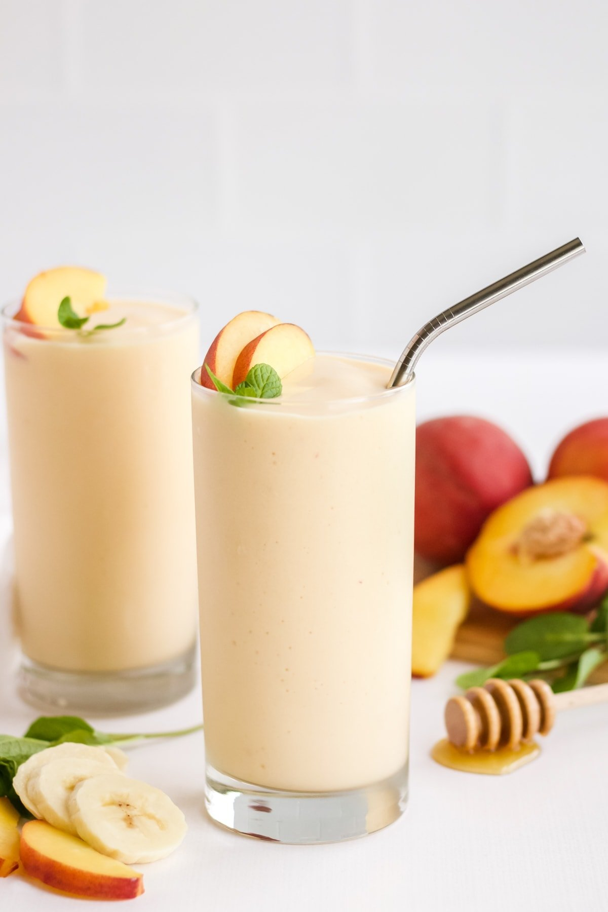 A picture of two peach banana smoothies with ingredients laid out around them and a white backdrop