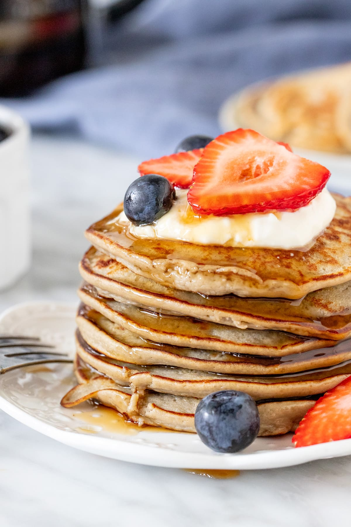 Stack of protein pancakes with syrup dripping down the sides.