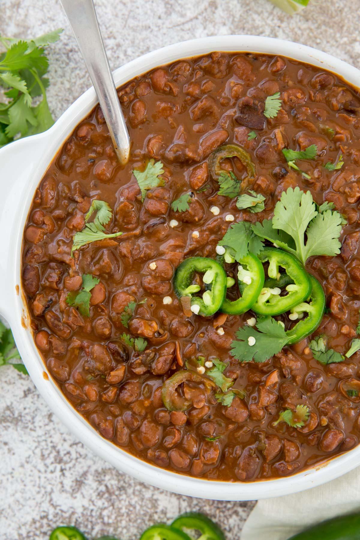 white bowl, pinto beans, jalapeno, cilantro, silver spoon
