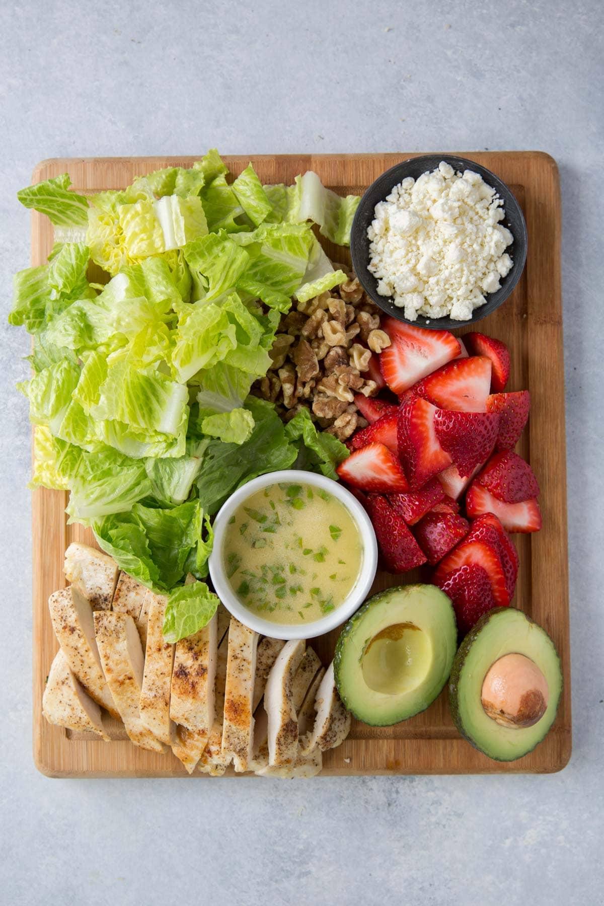 lettuce, feta, avocado, vinaigrette chicken, strawberries, walnut, on a wood cutting board