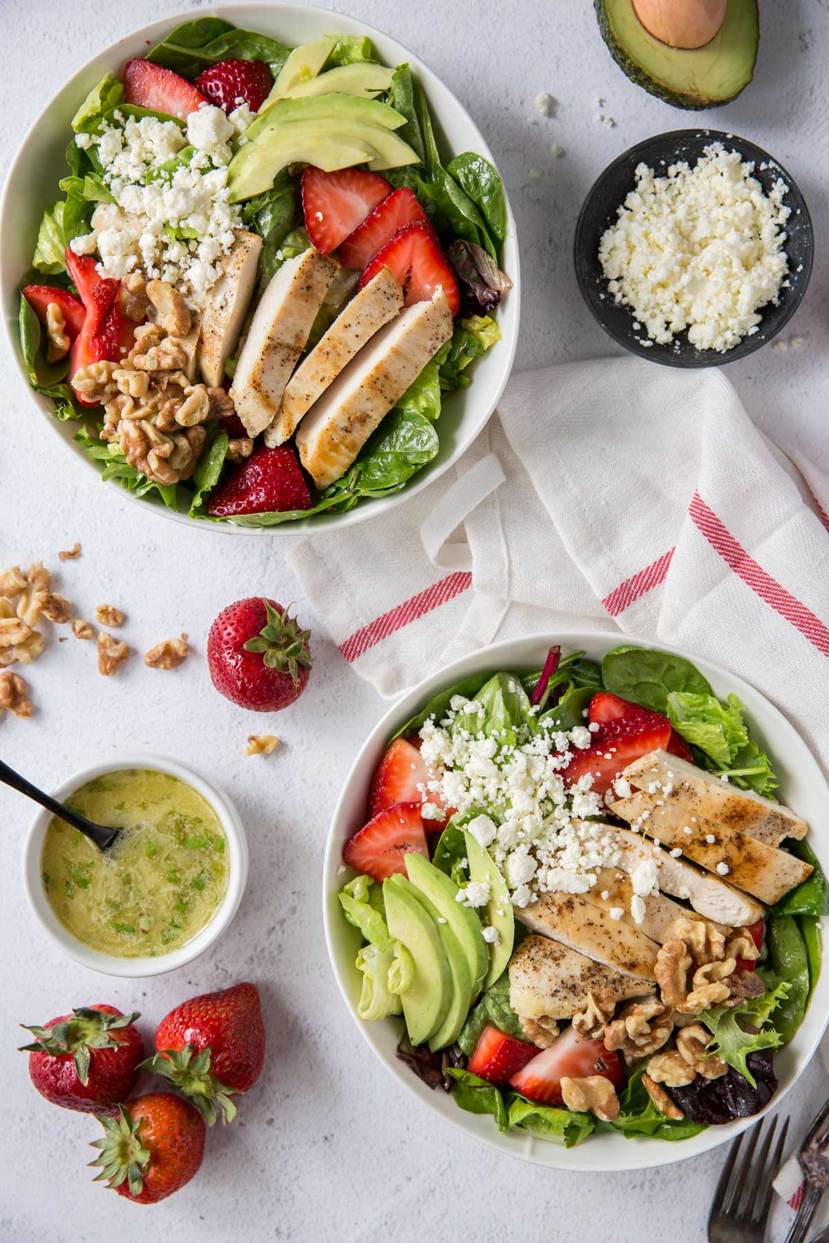 two white bowls with salad, chicken, strawberries, avocado, feta, dressing, forks