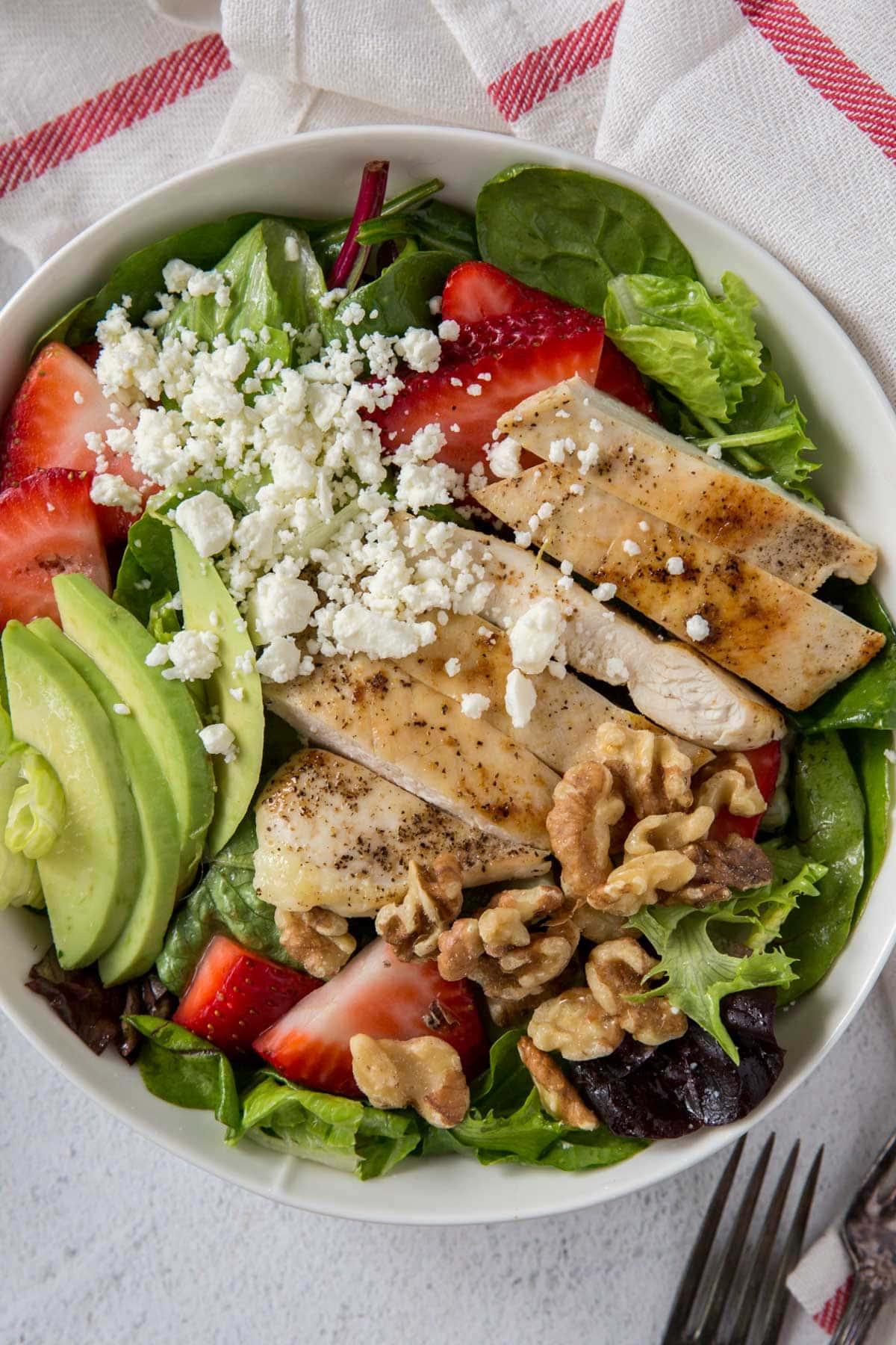 overhead of strawberry chicken salad with avocado, chicken, feta, lettuce, white bowl
