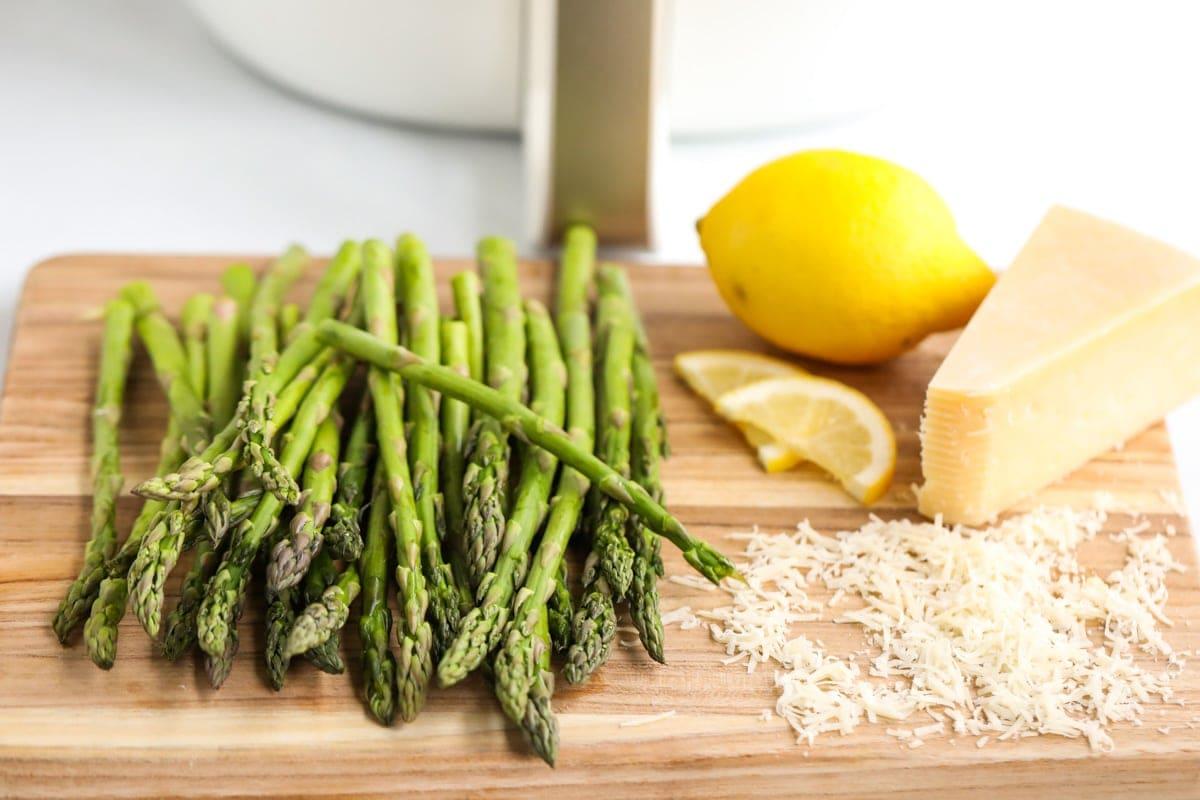 wood cutting board, lemon, parmesan cheese, asparagus